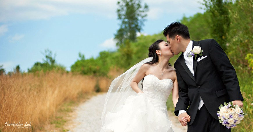 Christopher Luk 2011 - Jenny and James' Wedding - Trinity Presbyterian Church York Mills, Evergreen Brick Works, Renaissance by the Creek Toronto Mississauga - Bride and Groom Creative Relaxed Portrait Session Kiss Green Grass Blue Sky