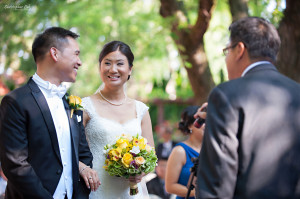 Christopher Luk 2013 - Victoria and Wallace's Wedding - Outdoor Summer Garden Wedding - Sala Caboto at The Columbus Event Centre - Bride and Groom Ceremony Photojournalistic Candid Smiling Looking at Each Other Pastor Officiant Exhortation