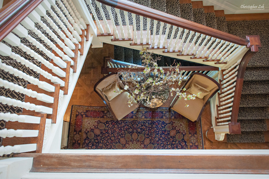 Christopher Luk - Toronto Wedding Portrait Event Photographer - Graydon Hall Manor - Staircase Overhead View Banister Chairs Floral Arrangement Side Table Persian Rug Carpet