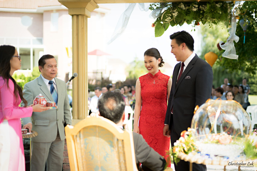 Christopher Luk 2015 - Vannessa and Daniel's Brampton Summer Outdoor Backyard Tea Ceremony Family Wedding Engagement Party Celebration - Bride Groom Navy Blue Suit Asian Red Dress Tea Ceremony Smile Laugh Candid Photojournalistic