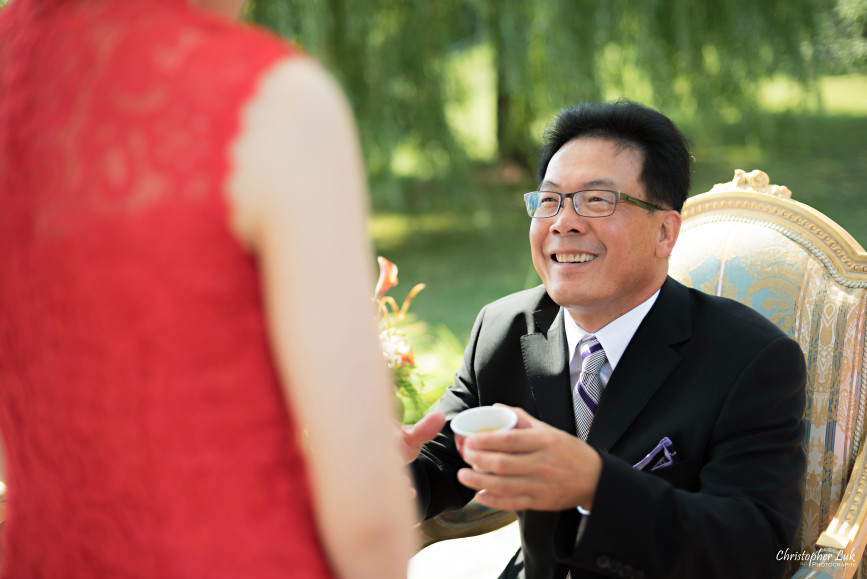 Christopher Luk 2015 - Vannessa and Daniel's Brampton Summer Outdoor Backyard Tea Ceremony Family Wedding Engagement Party Celebration - Bride Groom Navy Blue Suit Asian Red Dress Tea Ceremony Smile Laugh Candid Photojournalistic Father Daughter in Law Cup