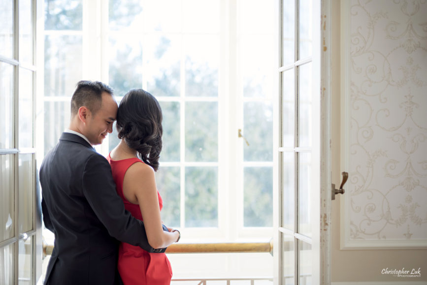 Christopher Luk (Toronto Wedding Photographer): Winter Indoor Engagement Session PreWedding Pictures Heintzman House Photos Markham York Region Natural Candid Photojournalistic Bride Groom Hug Balcony Window Doors Hold Close Snuggle