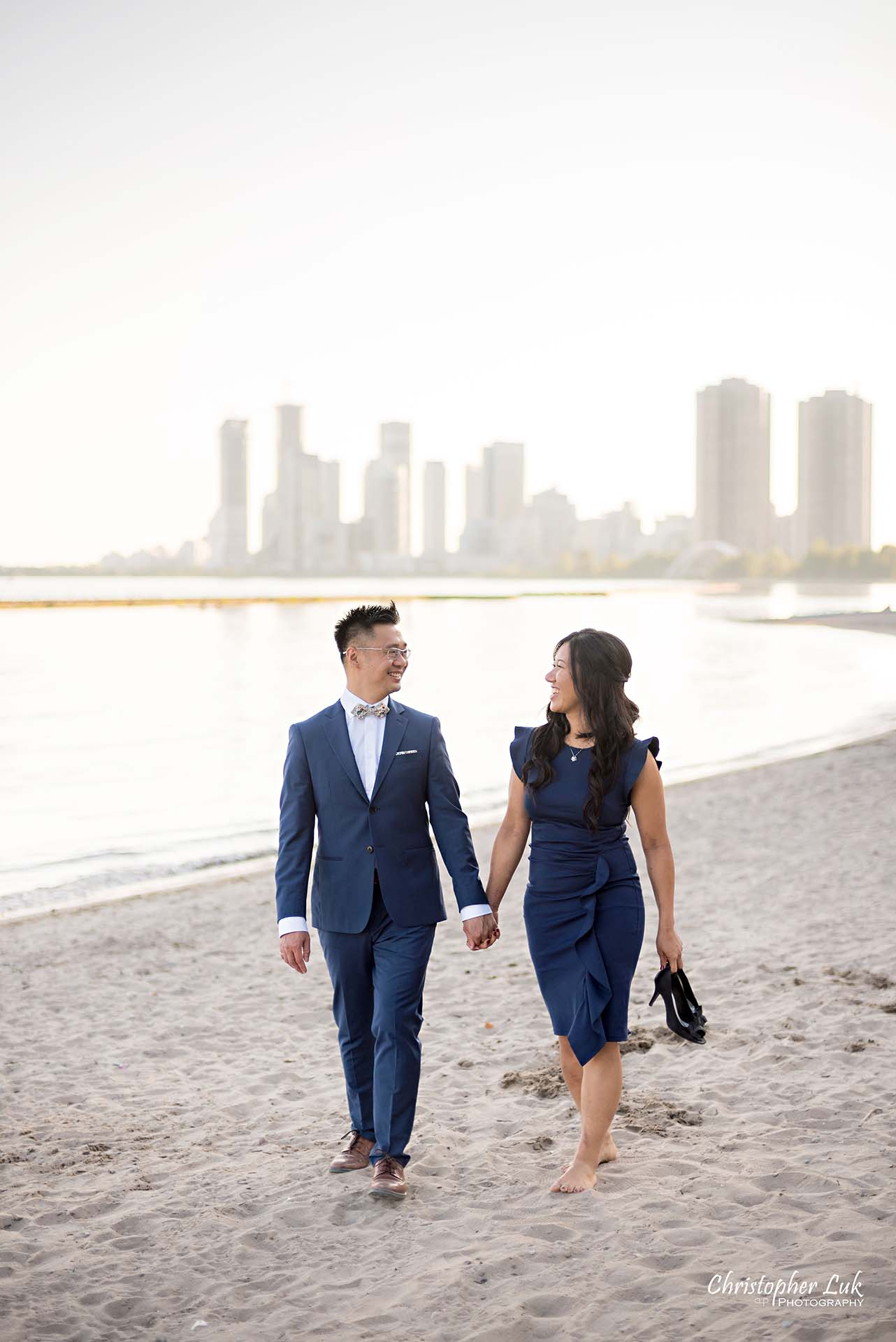 Christopher Luk Toronto Wedding Photographer - Engagement Photography - Sunnyside Pavilion Park Beach Boardwalk Toronto - Bride and Groom Natural Candid Photojournalistic Humber Bay Archway Arch Bridge Skyline Walking Vertical Holding Shoes