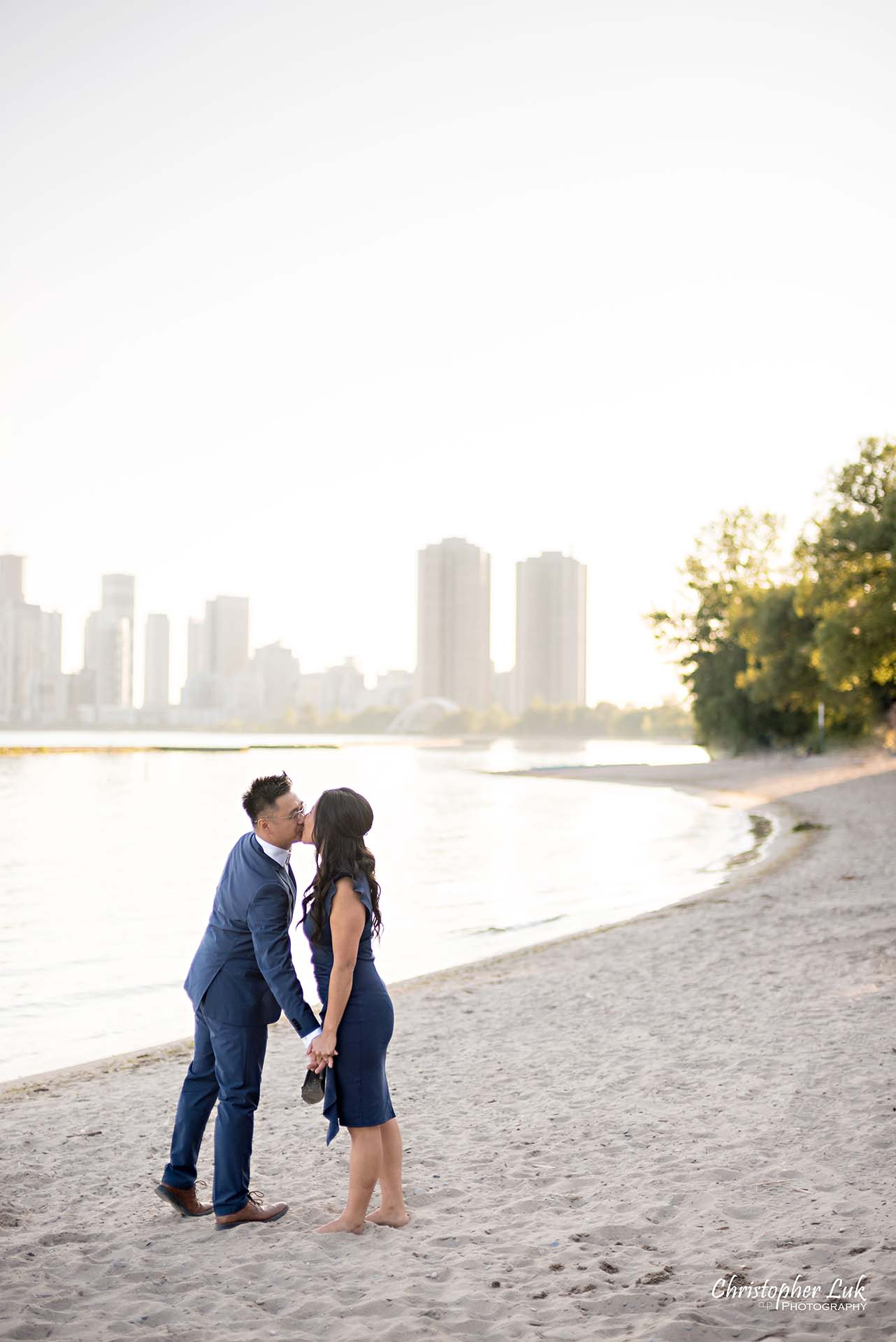 Christopher Luk Toronto Wedding Photographer - Engagement Photography - Sunnyside Pavilion Park Beach Boardwalk Toronto - Bride and Groom Natural Candid Photojournalistic Humber Bay Archway Arch Bridge Skyline Walking Kiss