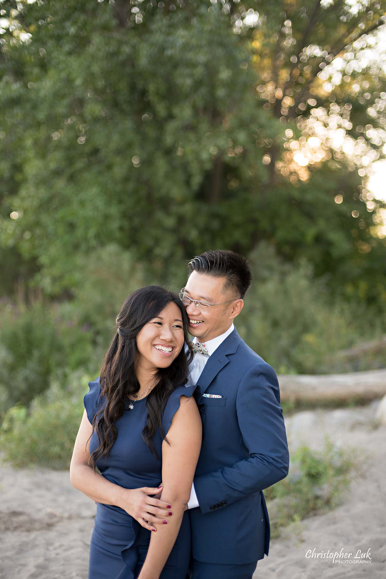 Christopher Luk Toronto Wedding Photographer - Engagement Photography - Sunnyside Pavilion Park Beach Boardwalk Toronto - Bride and Groom Natural Candid Photojournalistic Hug Smile Trees Close Love Hands Hold