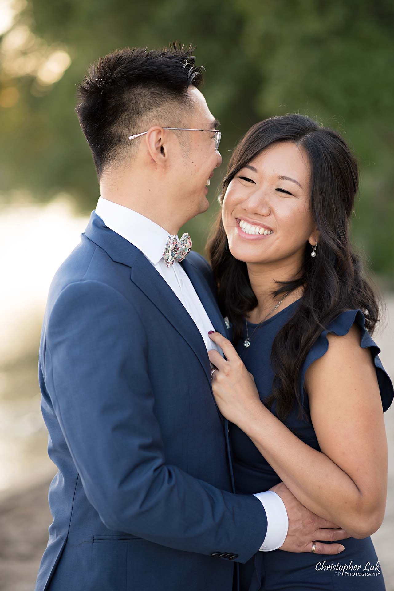Christopher Luk Toronto Wedding Photographer - Engagement Photography - Sunnyside Pavilion Park Beach Boardwalk Toronto - Bride and Groom Natural Candid Photojournalistic Hug Smile Trees Close