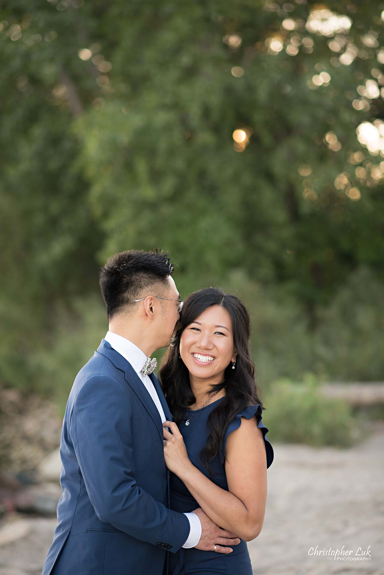 Christopher Luk Toronto Wedding Photographer - Engagement Photography - Sunnyside Pavilion Park Beach Boardwalk Toronto - Bride and Groom Natural Candid Photojournalistic Hug Smile Trees