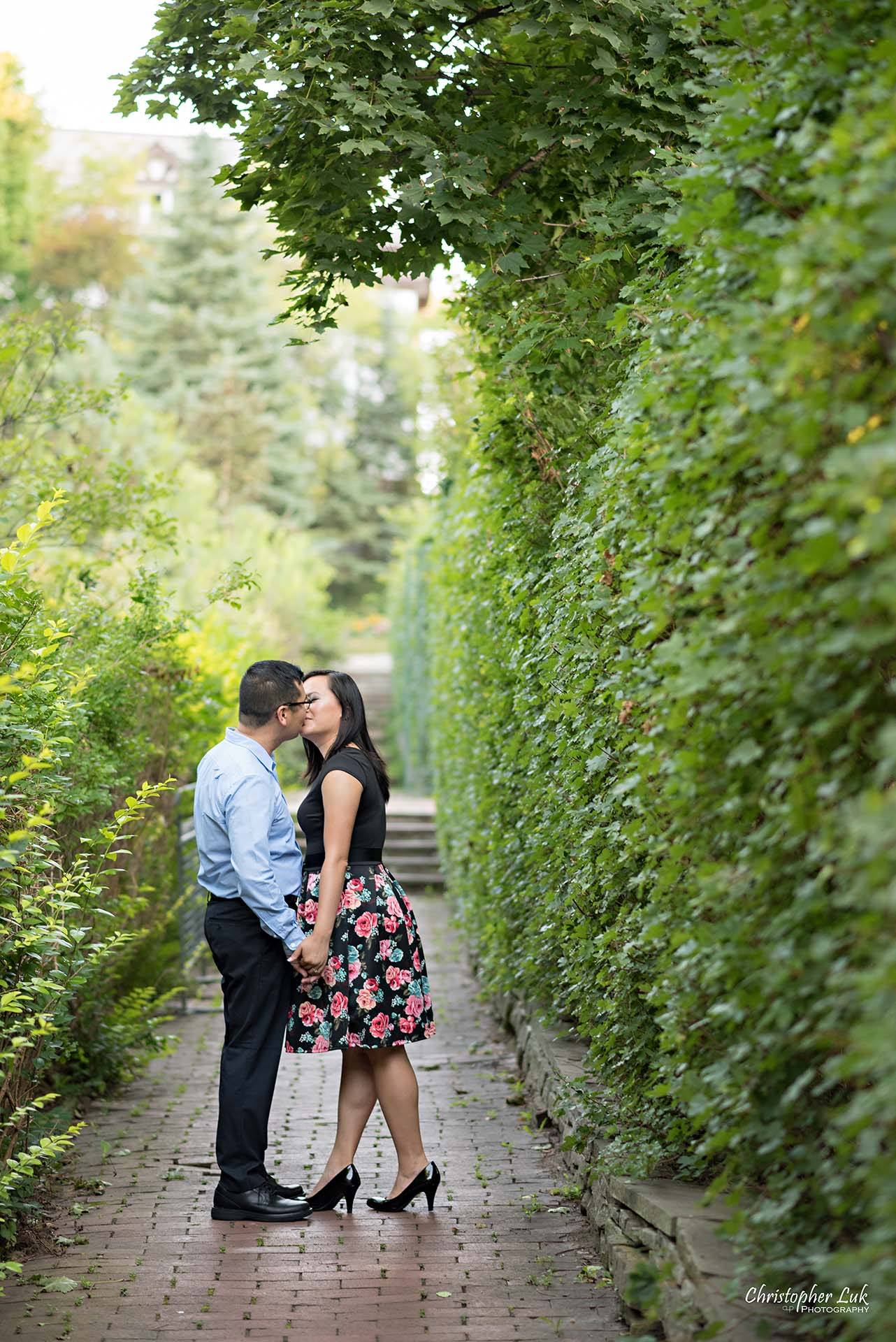 Christopher Luk Toronto Wedding Family Event Corporate Commercial Headshot Photographer Edith Jeff Engagement Session Alexander Muir Memorial Gardens Park MidTown Photo Location Natural Candid Photojournalistic - Bride and Groom Walking Forest Pathway Path Kiss