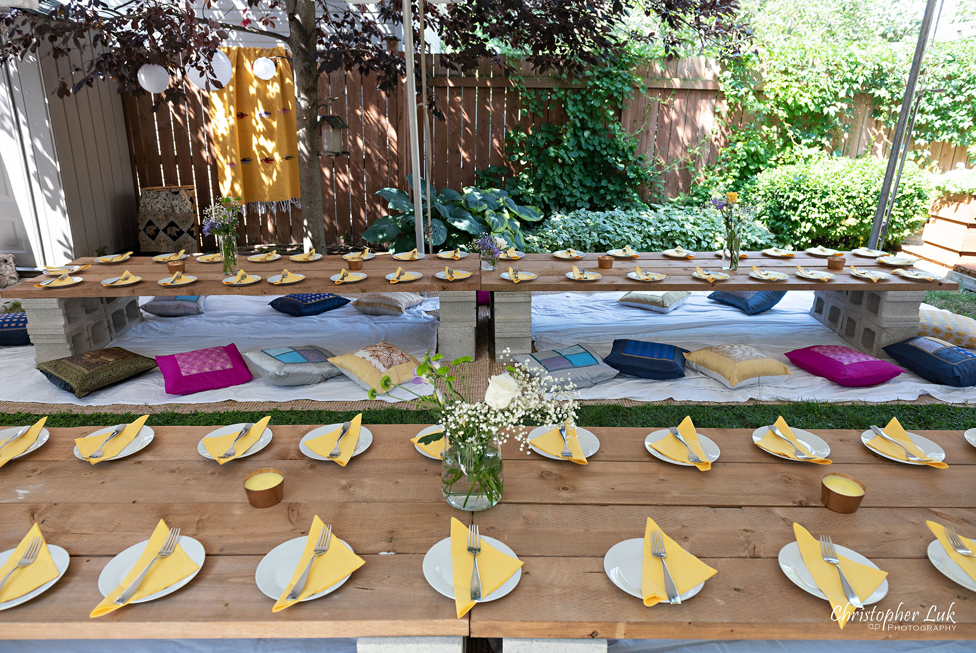 Christopher Luk Toronto Wedding Engagement Event Photographer Bohemian Boho Chic Backyard Tent Wedding Wood Table Planks Folded Napkins Plates Floral Centrepieces Coloured Pillows Floor Mats Detail