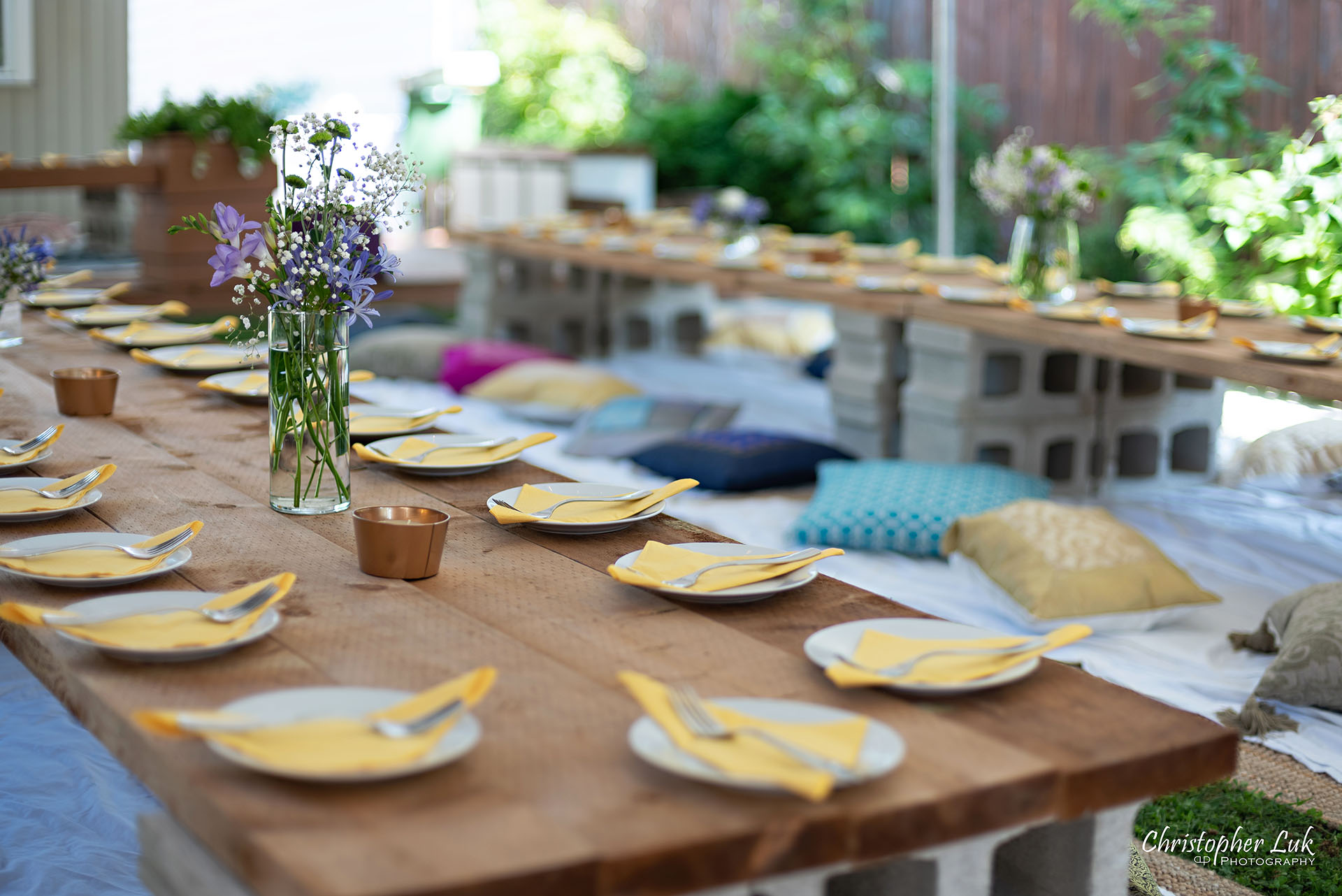 Christopher Luk Toronto Wedding Engagement Event Photographer Bohemian Boho Chic Backyard Tent Wedding Wood Table Planks Folded Napkins Plates Floral Centrepieces Coloured Pillows Floor Mats Cement Cinder Block Stand Flowers Angle