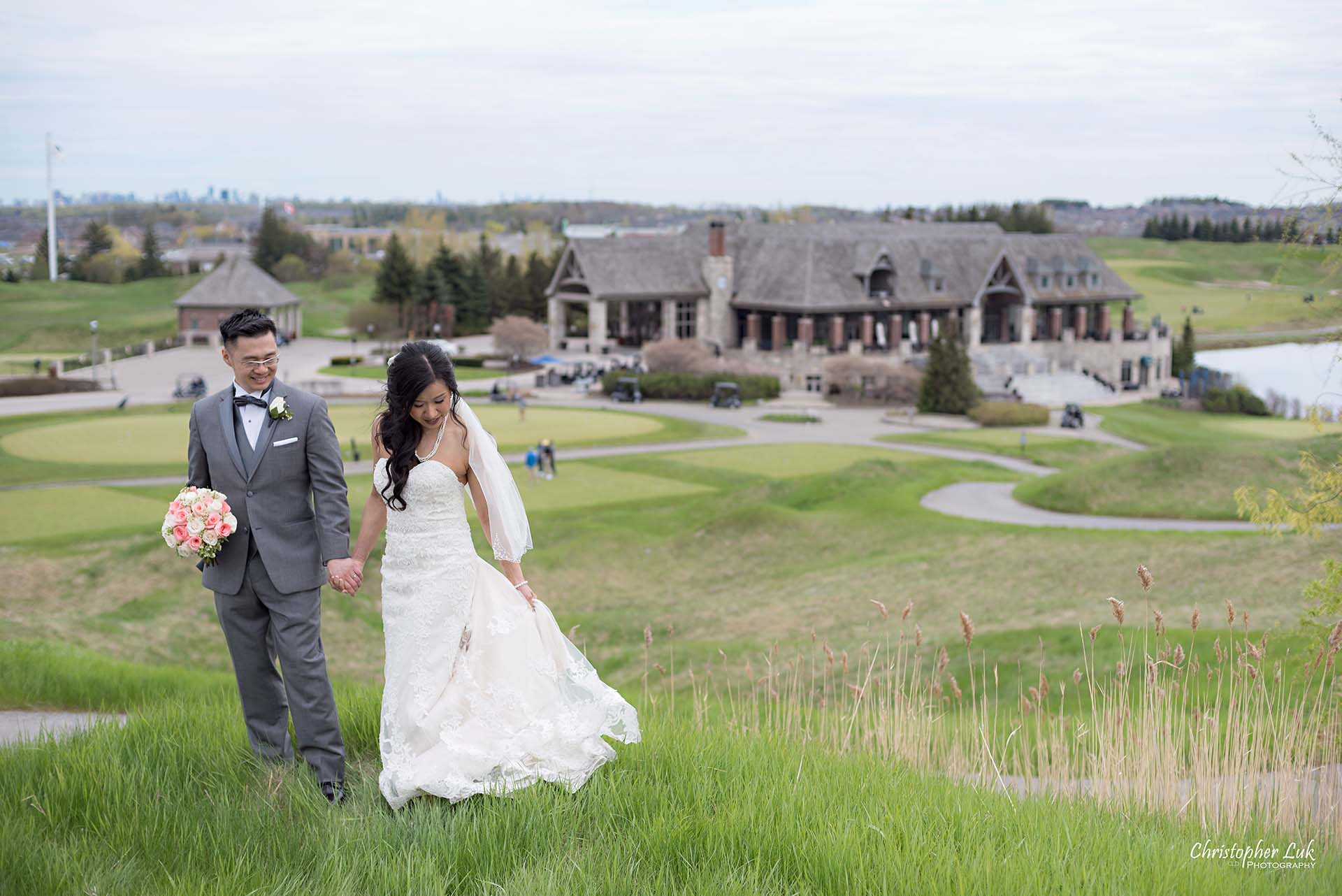 Christopher Luk Toronto Wedding Photographer Eagles Nest Golf Club Course Clubhouse Walking Climbing Up a Grassy Hill Together Bride Groom Holding Hands Scenic Landscape Wide