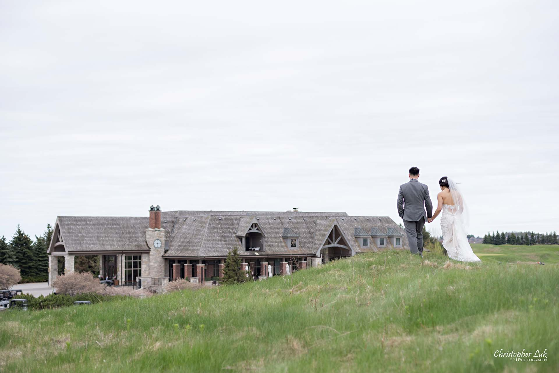 Christopher Luk Toronto Wedding Photographer Eagles Nest Golf Club Course Clubhouse Walking Climbing Up a Grassy Hill Together Bride Groom Holding Hands Journey