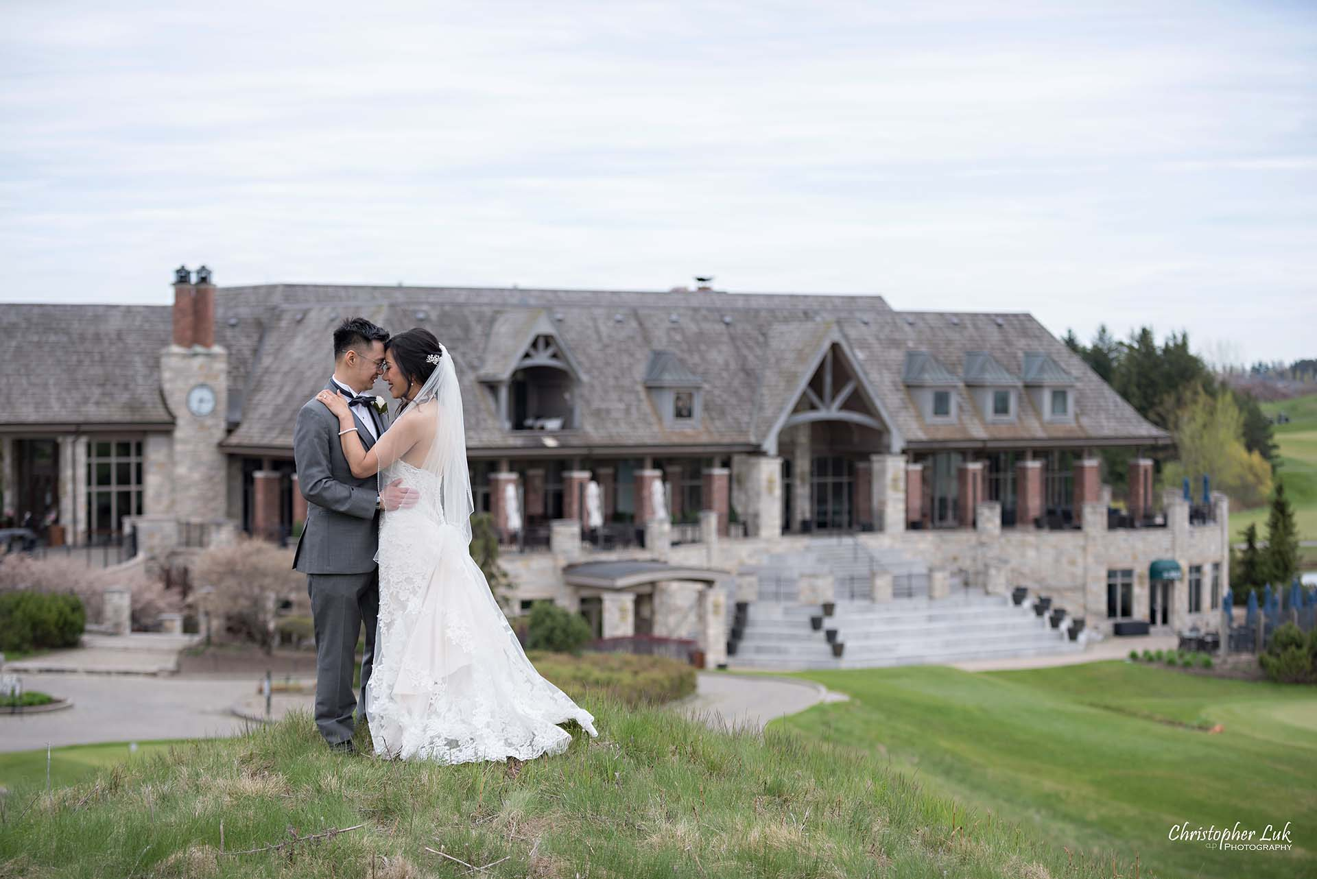 Christopher Luk Toronto Wedding Photographer Eagles Nest Golf Club Course Clubhouse Walking Climbing Up a Grassy Hill Together Bride Groom Hold Hug Scenic Landscape