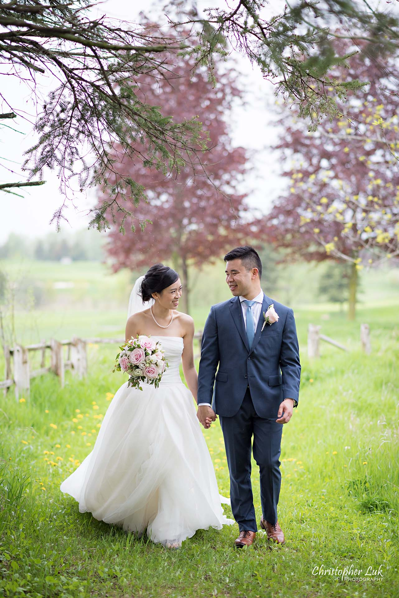 Christopher Luk Toronto Wedding Photographer Angus Glen Golf Club Markham Main Blue Barn Farm Historic Estate Building Together Natural Candid Photojournalistic Bride Groom Holding Hands Together Walking Green Grass Pathway Portrait