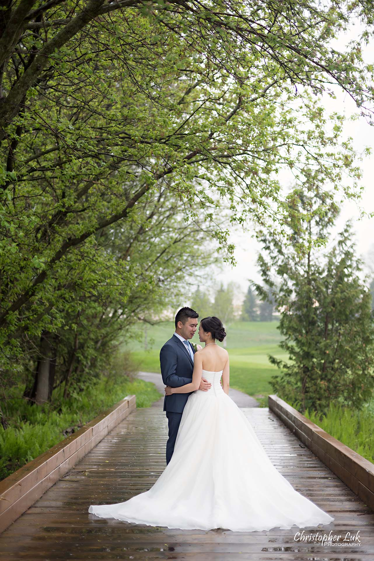 Christopher Luk Toronto Wedding Photographer Angus Glen Golf Club Markham Great Hall Dinner Reception Event Venue Green Field Sunset Bride Groom Natural Candid Photojournalistic Wooden Bridge Green Arch Trees Holding Each Other Hug Bridal Dress Gown Train Portrait