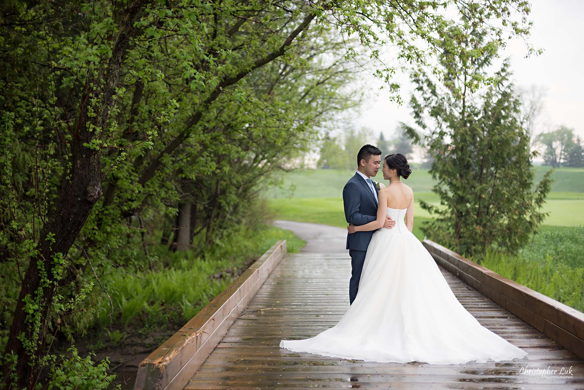 Christopher Luk Toronto Wedding Photographer Angus Glen Golf Club Markham Great Hall Dinner Reception Event Venue Green Field Sunset Bride Groom Natural Candid Photojournalistic Wooden Bridge Green Arch Trees Holding Each Other Hug Bridal Dress Gown Train Landscape