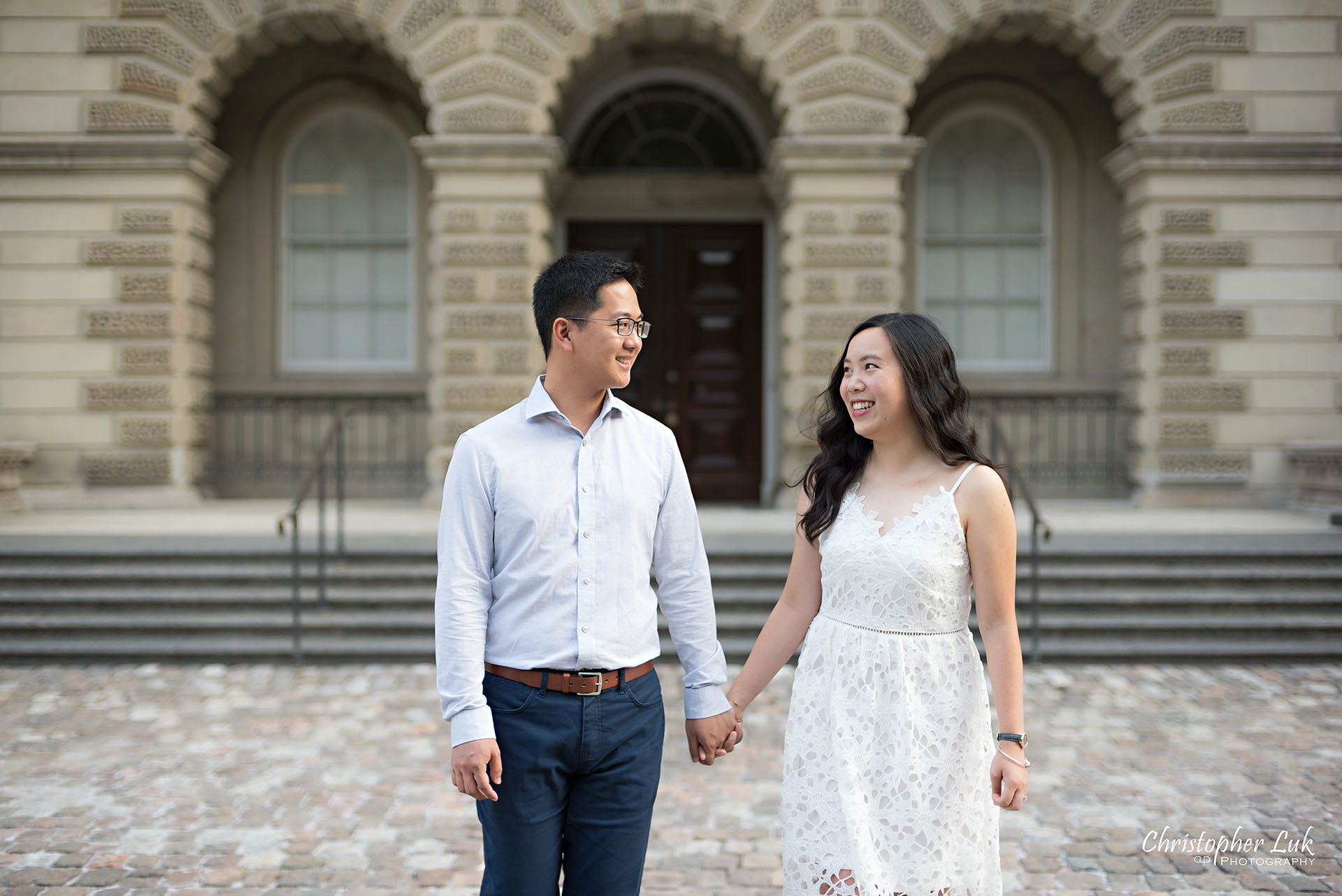 Christopher Luk Wedding Photographer Osgoode Hall Toronto Bride Groom Main Historic Building Front Cobblestone Holding Hands Walking Together Christopher Luk Wedding Photographer Osgoode Hall Toronto Bride Groom Main Historic Building Front Cobblestone Holding Hands Walking Together Looking at Each Other Portrait Natural Candid Photojournalistic