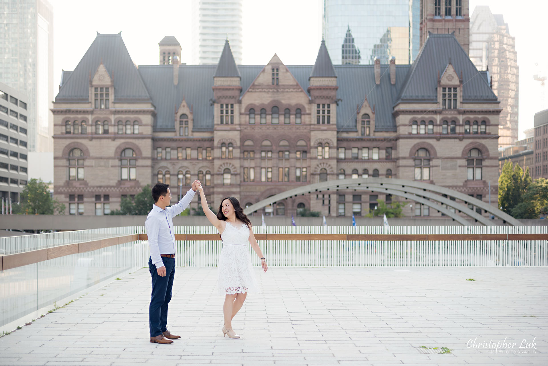 Christopher Luk Wedding Photographer Toronto City Hall Nathan Philips Square Elevated Bridge Arches Archway Bride Groom Holding Hands Walking Together Laughing Dancing Twirl Spin Intimate Natural Candid Photojournalistic Wide Landscape