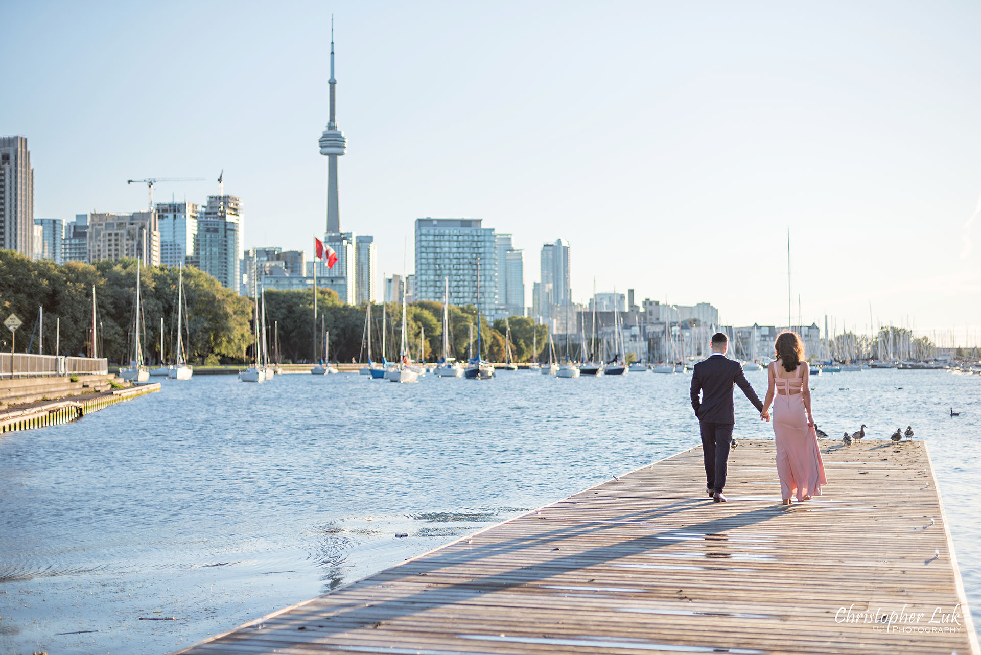 Christopher Luk Trillium Park Ontario Place Waterfront Engagement Session Toronto Wedding Photographer Bride Groom Natural Candid Photojournalistic Boat Dock CN Tower Skyline Background Sunrise Walking Together Hotel X