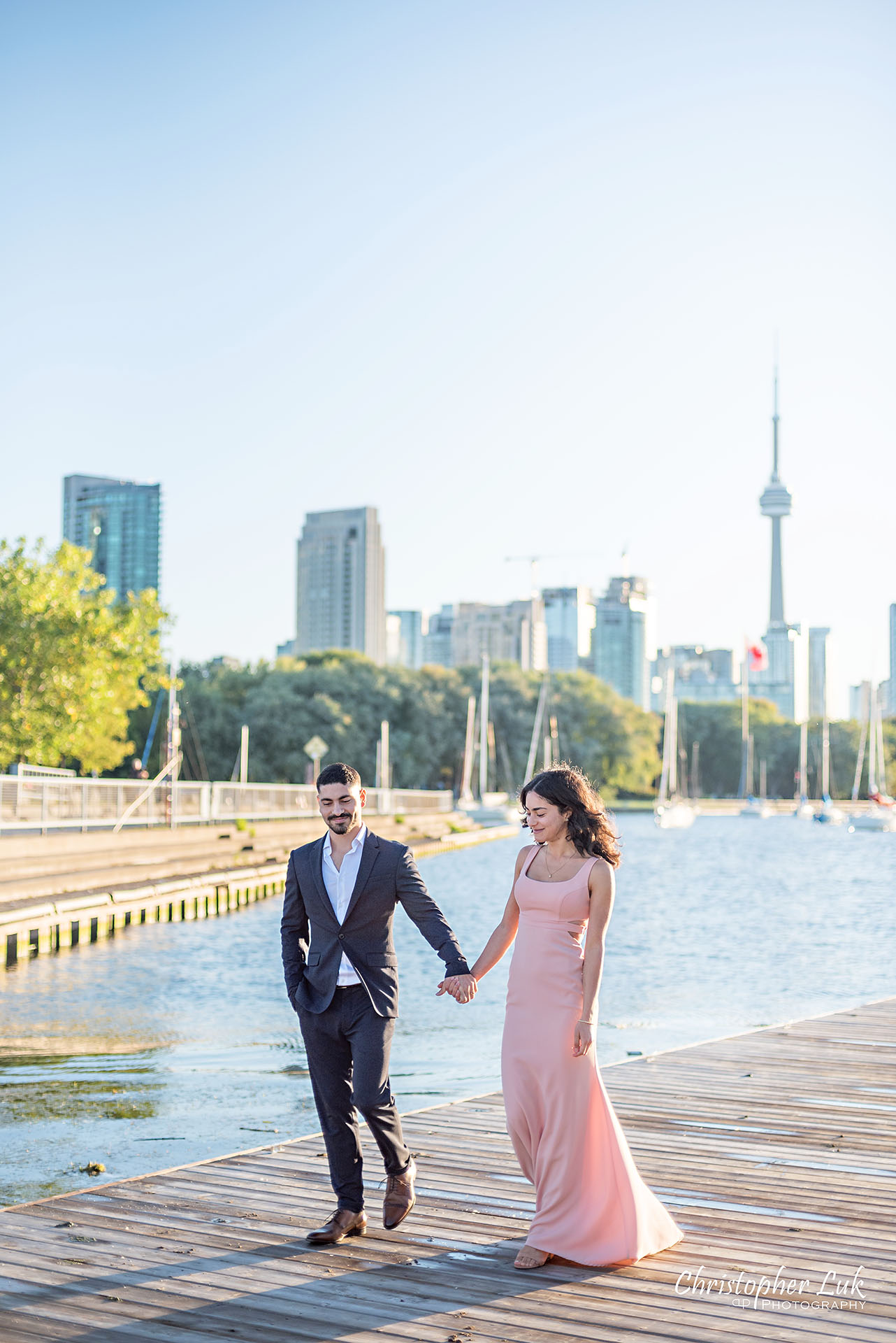 Christopher Luk Trillium Park Ontario Place Waterfront Engagement Session Toronto Wedding Photographer Bride Groom Natural Candid Photojournalistic Boat Dock CN Tower Skyline Background Sunrise Kiss Vertical Portrait Hotel X