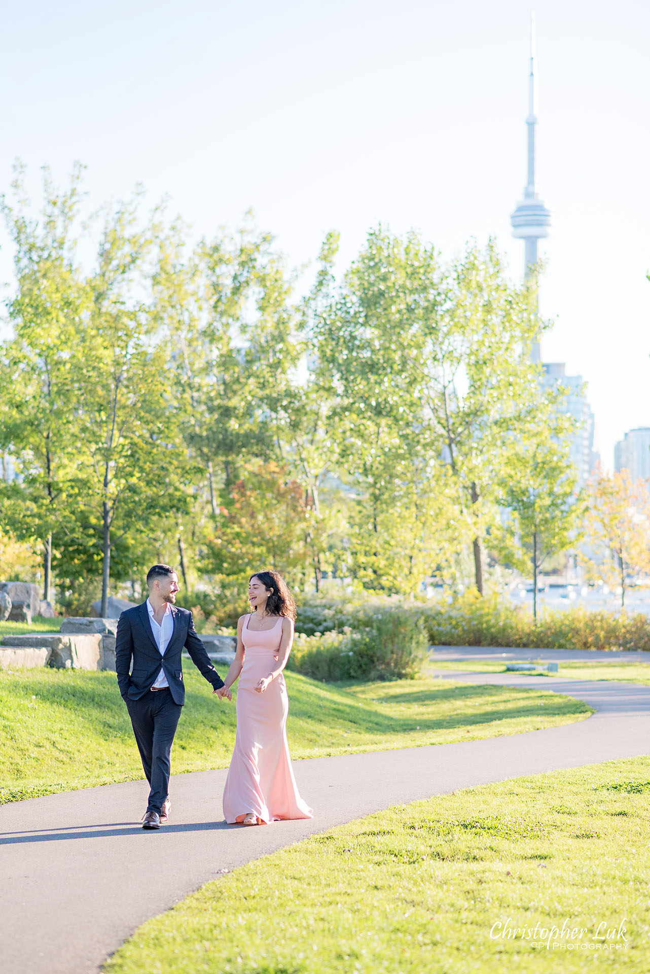 Christopher Luk Trillium Park Ontario Place Waterfront Engagement Session Toronto Wedding Photographer Bride Groom Natural Candid Photojournalistic CN Tower Skyline Background Trees Sunrise Walkway Path Trail Vertical Portrait