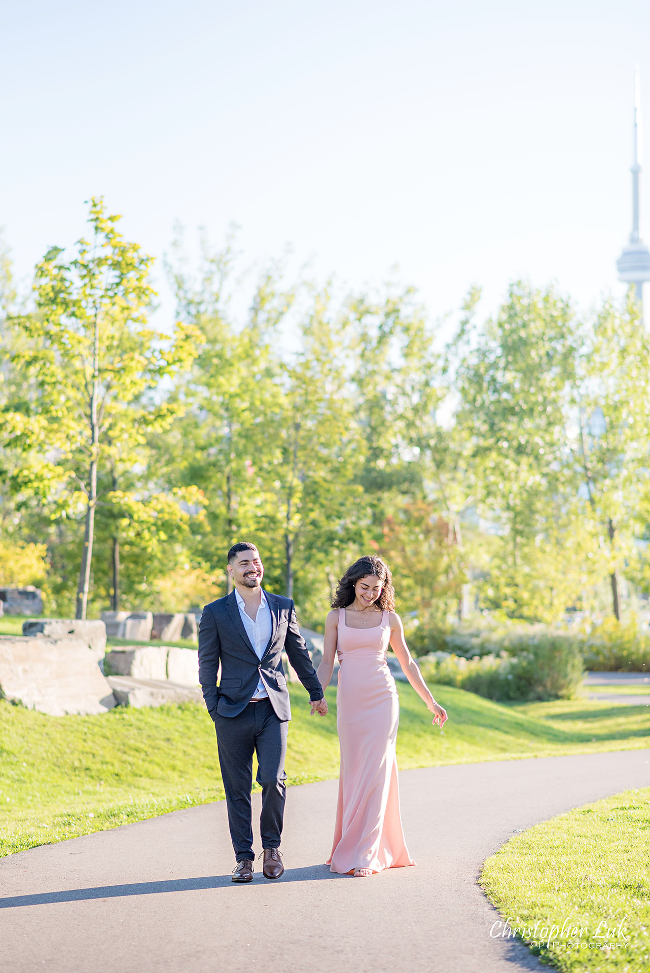 Christopher Luk Trillium Park Ontario Place Waterfront Engagement Session Toronto Wedding Photographer Bride Groom Natural Candid Photojournalistic CN Tower Skyline Background Trees Sunrise Walkway Path Trail Vertical Portrait Laugh