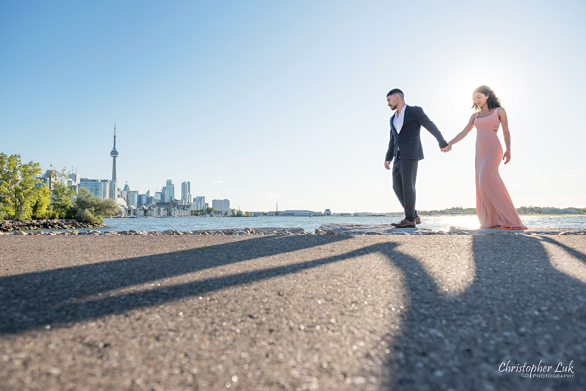 Christopher Luk Trillium Park Ontario Place Waterfront Engagement Session Toronto Wedding Photographer Bride Groom Natural Candid Photojournalistic CN Tower Skyline Background Sunrise Walkway Pathway Shadows