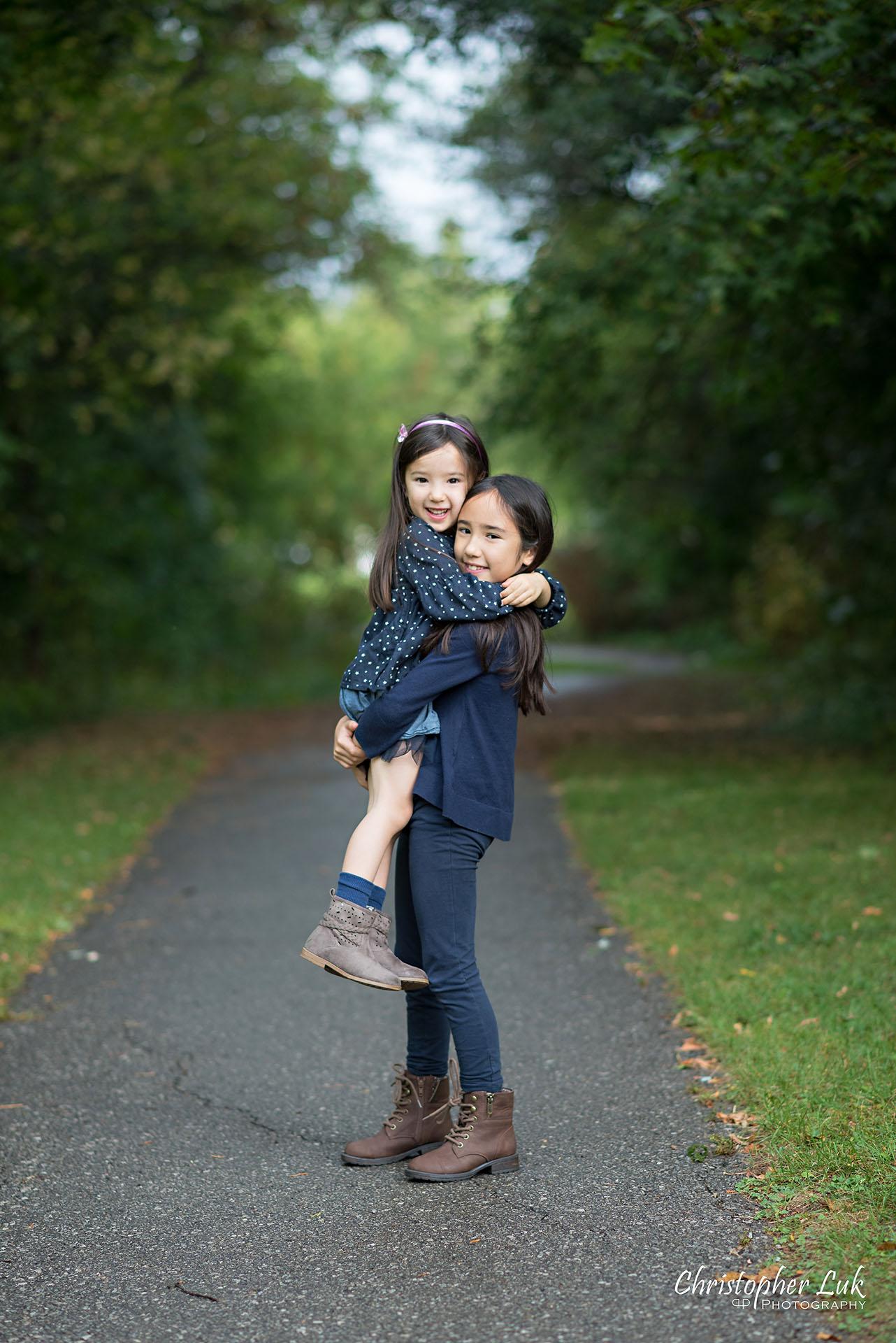 Christopher Luk Family Photographer Toronto Markham Candid Natural Photojournalistic Daughters Sisters Sisterhood Smile Hug Carry Lift Cute Adorable