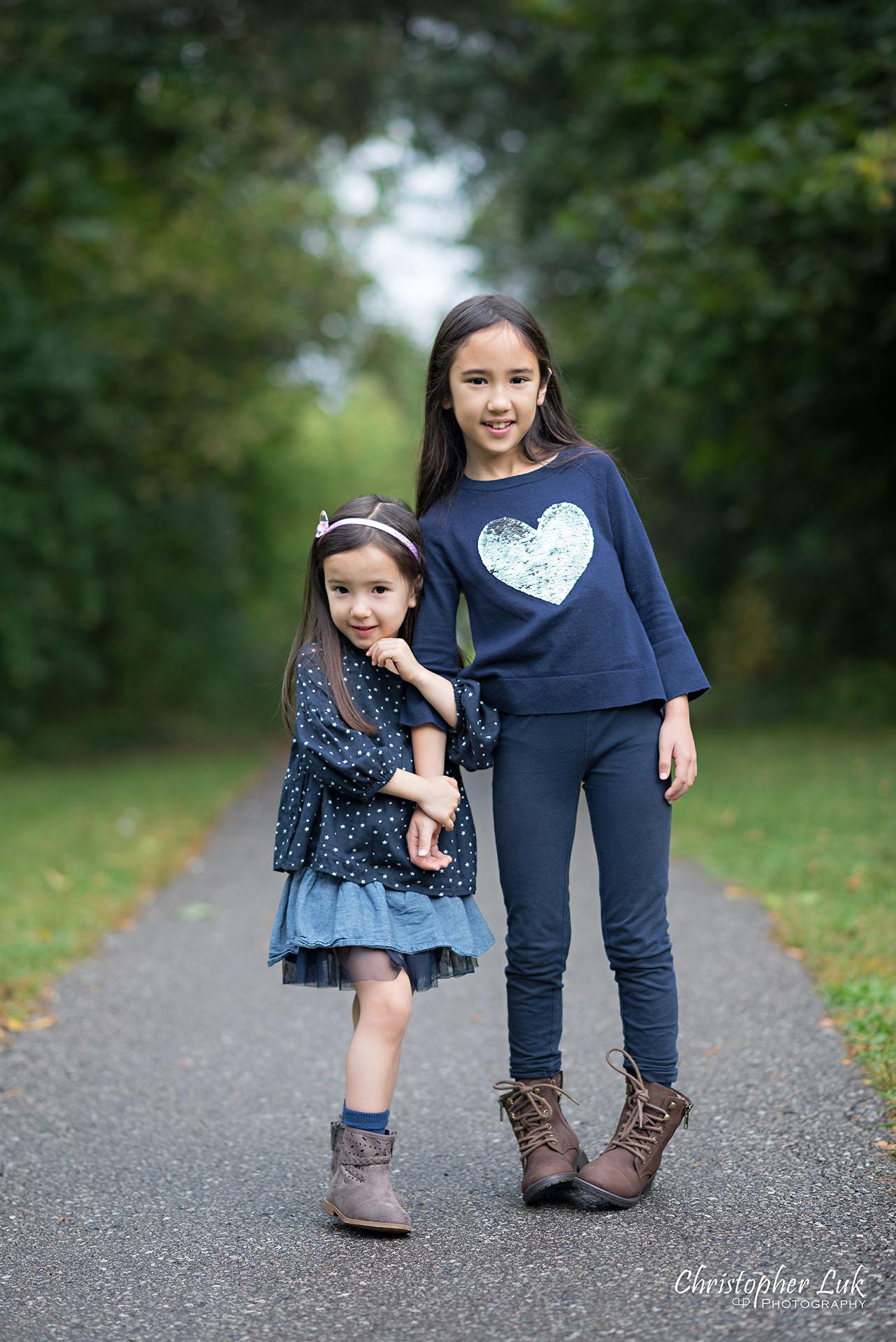 Christopher Luk Family Photographer Toronto Markham Candid Natural Photojournalistic Daughters Sisters Sisterhood Smile Hug Hugging Holding Arms Cute Adorable