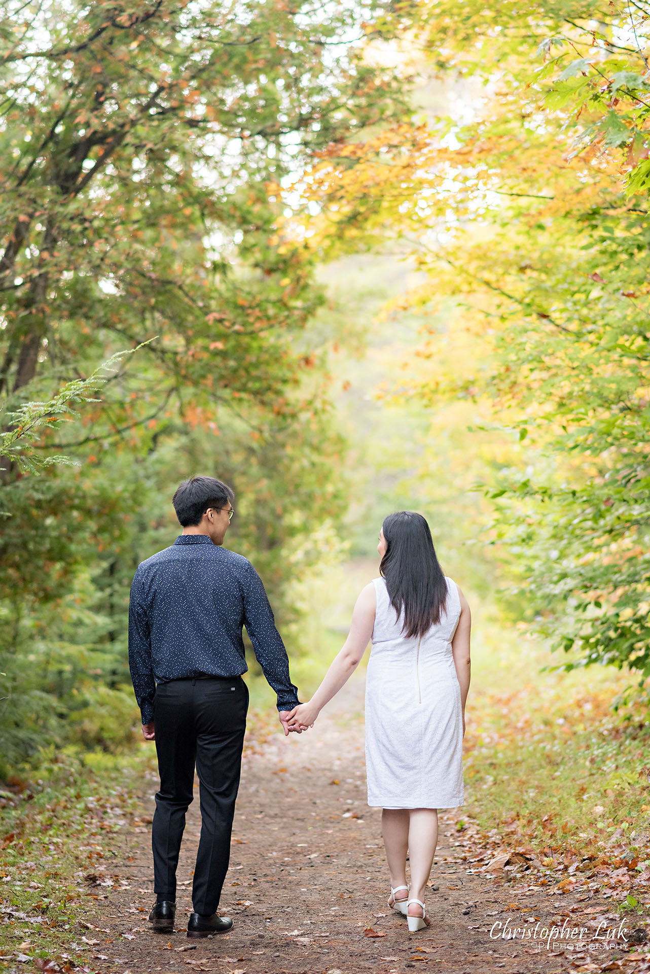 Christopher Luk Toronto Wedding Photographer Stouffville Forest Conservation Park Engagement Session Candid Natural Photojournalistic Bride Groom Walking Together Holding Hands Autumn Fall Leaves Vertical