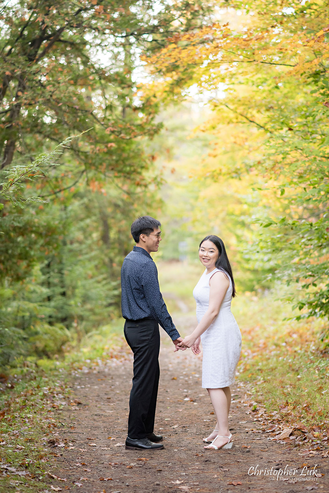 Christopher Luk Toronto Wedding Photographer Stouffville Forest Conservation Park Engagement Session Candid Natural Photojournalistic Bride Groom Walking Together Holding Hands Autumn Fall Leaves Smile Vertical