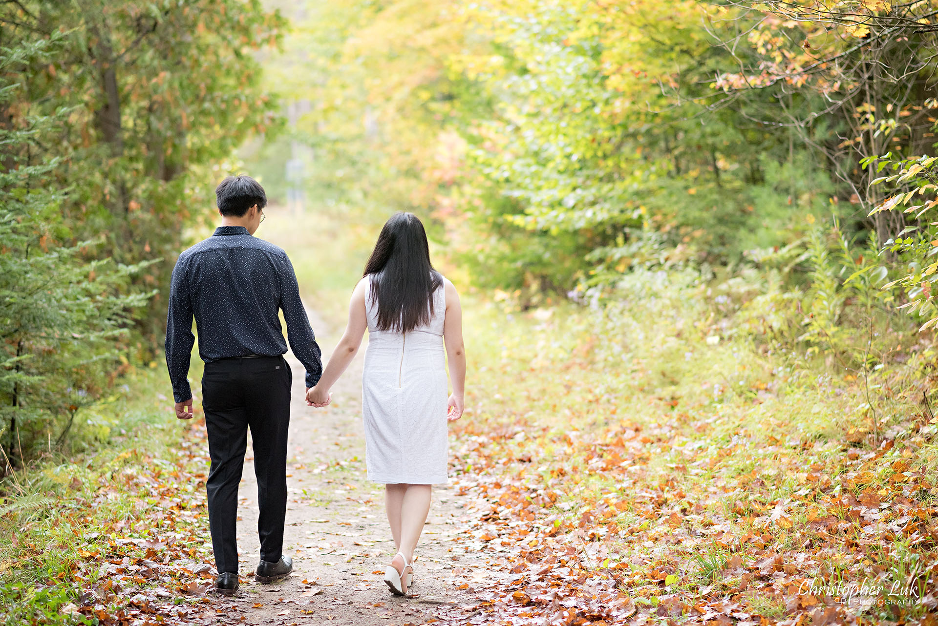 Christopher Luk Toronto Wedding Photographer Stouffville Forest Conservation Park Engagement Session Candid Natural Photojournalistic Bride Groom Walking Together Holding Hands Autumn Fall Leaves Landscape