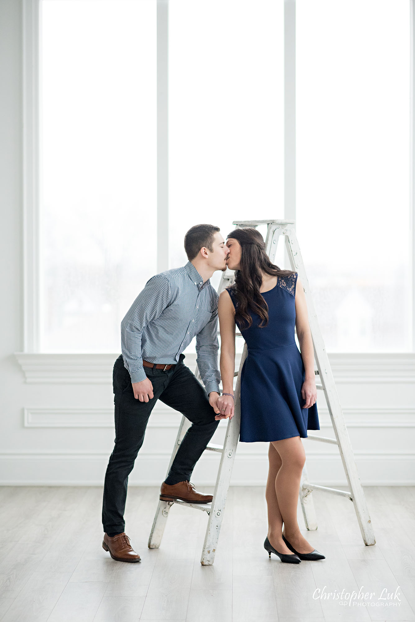 Christopher Luk Toronto Wedding Photographer Mint Room Studios Conservatory Engagement Session Winter Indoor Natural Light Candid Photojournalistic Bride Groom Vintage Rustic Ladder Window Holding Hands Kiss