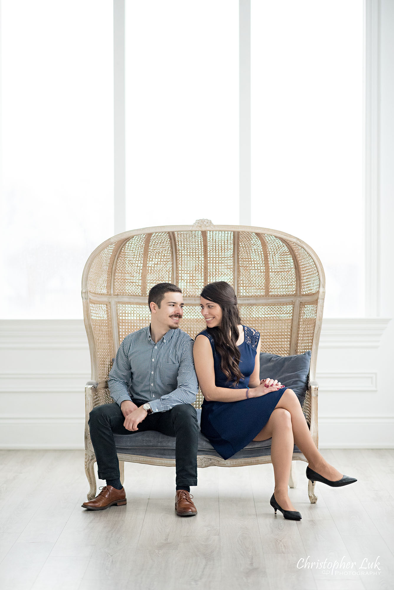 Christopher Luk Toronto Wedding Photographer Mint Room Studios Conservatory Engagement Session Winter Indoor Natural Light Candid Photojournalistic Bride Groom Wicker French Rustic Vintage Dome Loveseat Chair Looking at Each Other Lovingly