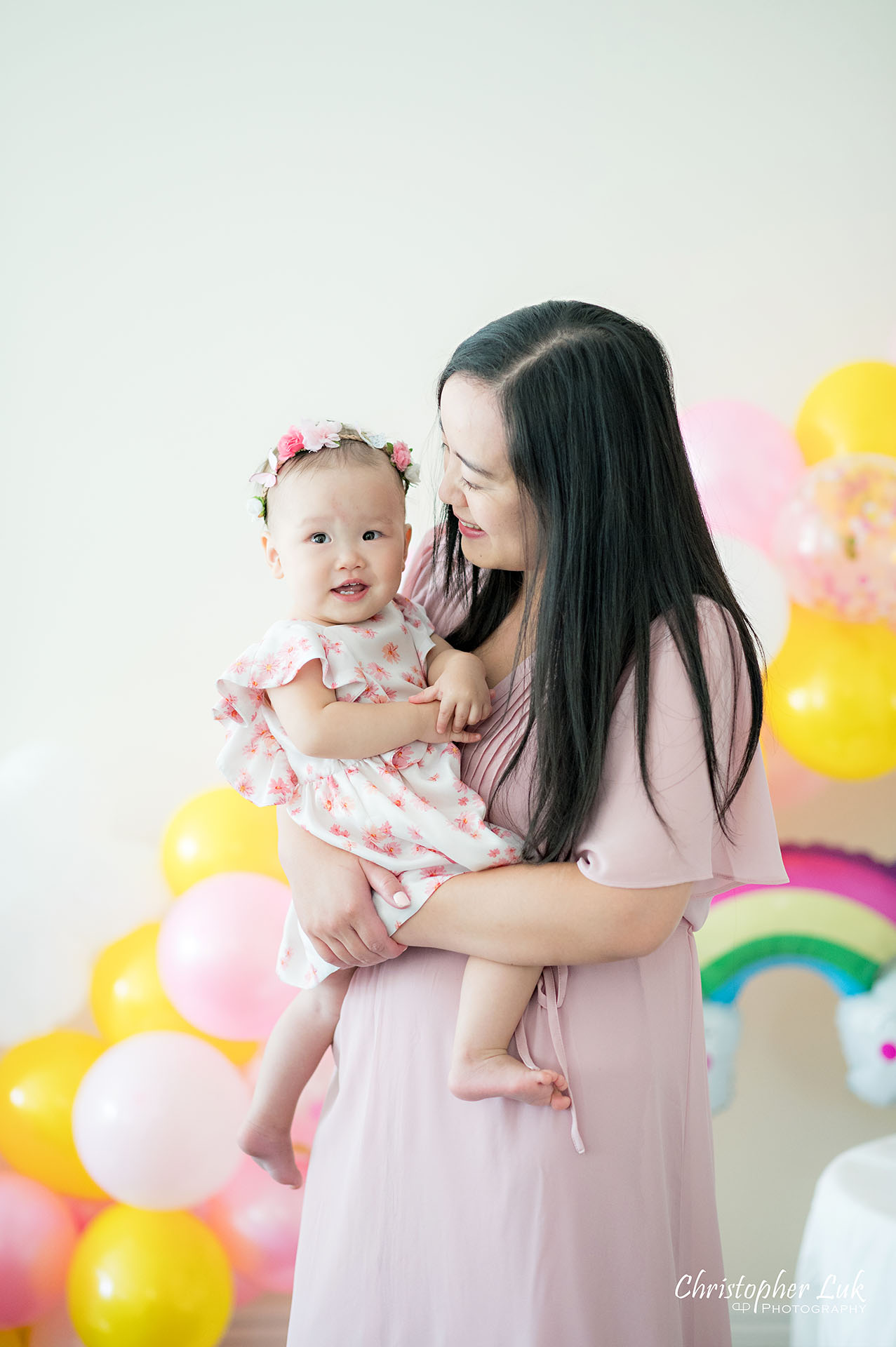 Christopher Luk Toronto Markham Family Photographer Baby Girl First Birthday Balloon Arch Rainbow Pink Sun Clouds Decor Mother Mom Daughter Motherhood Hug Smile Laugh Natural Candid Photojournalistic Portrait