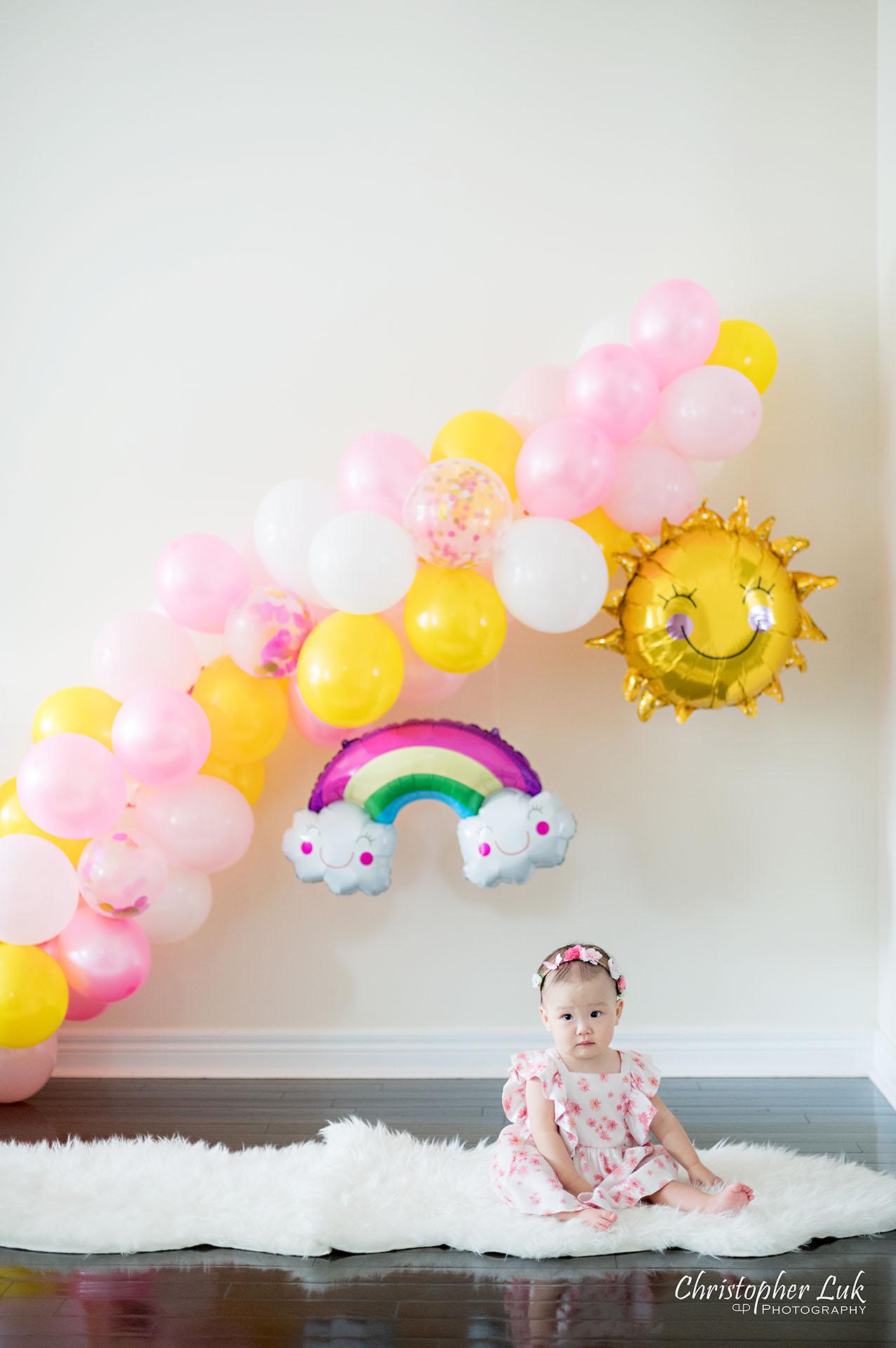 Christopher Luk Toronto Markham Family Photographer Baby Girl First Birthday Balloon Arch Rainbow Pink Sun White Fuzzy Fur Rug Mat Natural Candid Photojournalistic Portrait