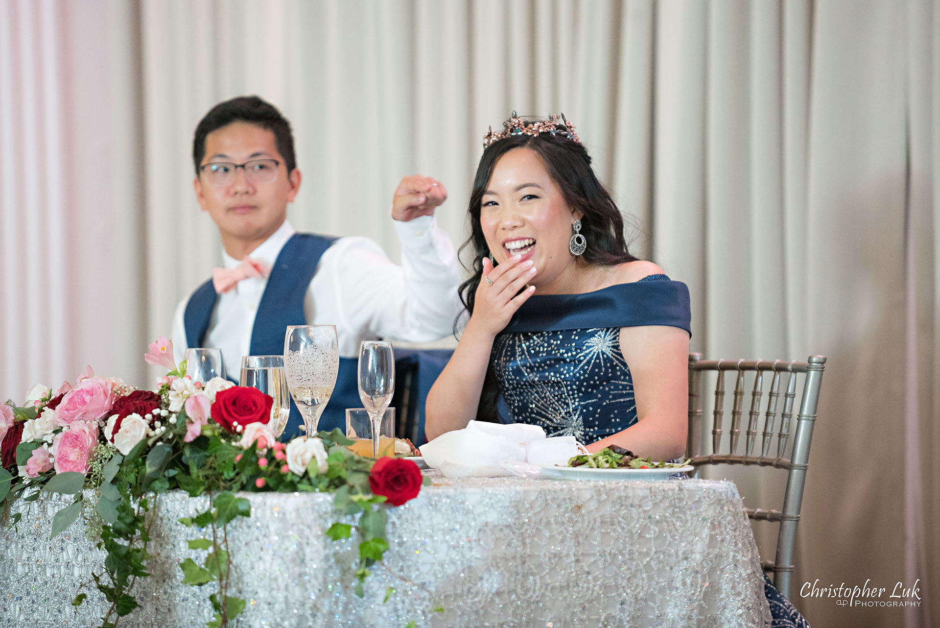 Christopher Luk Toronto Wedding Photographer Bridle Trail Baptist Church Unionville Main Street Crystal Fountain Event Venue Head Table Decor Flower Bell by Masami Crystal Linen Setup Wide Stage Curtains Bride Groom Speeches Laugh Reaction Pointing Funny