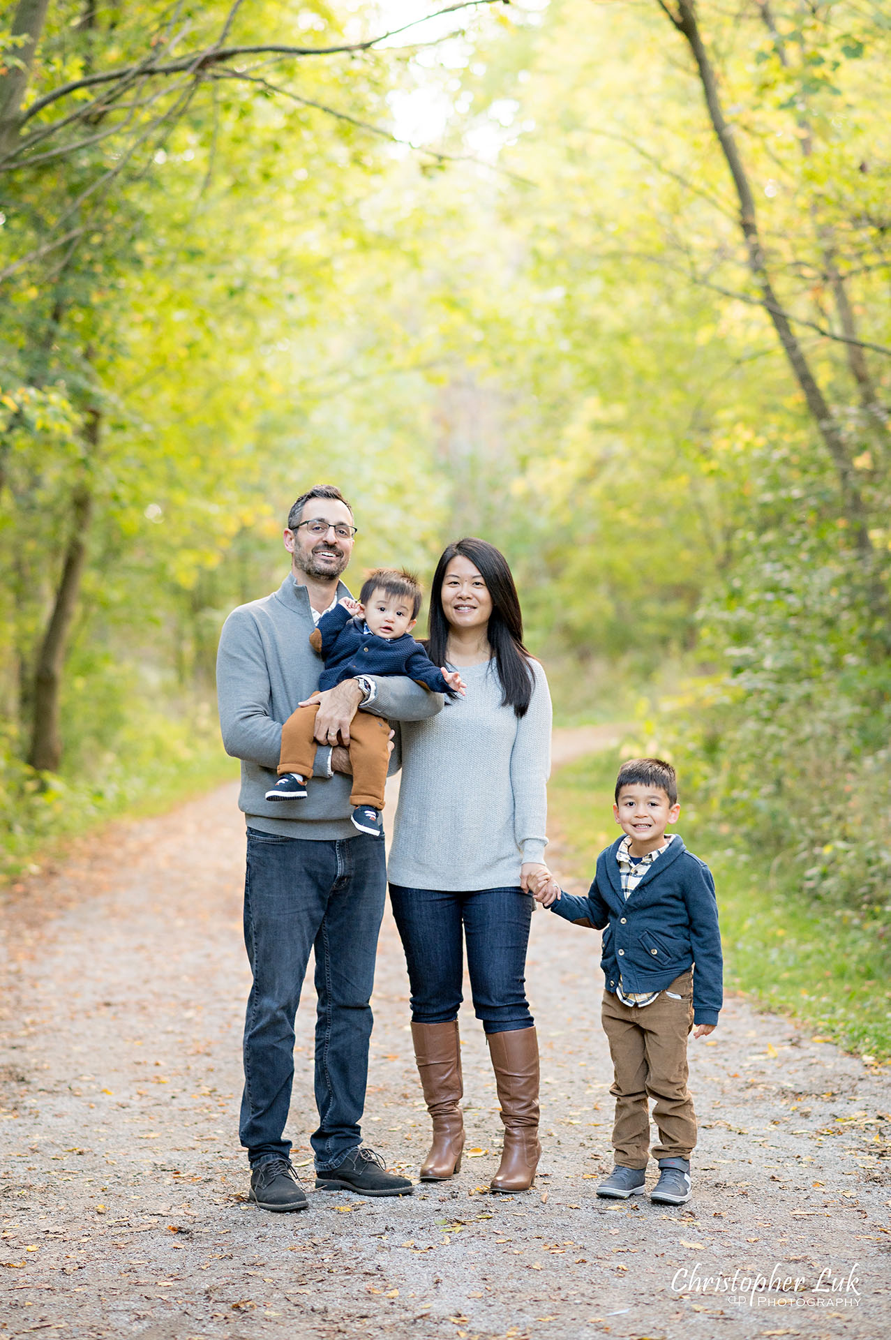 Christopher Luk Family Photographer Toronto Markham Unionville Autumn Fall Leaves Natural Candid Photojournalistic Sons Brothers Baby Boys Father Dad Mother Mom Motherhood Fatherhood Holding Hands Walking Together Trail Pathway Forest Smile