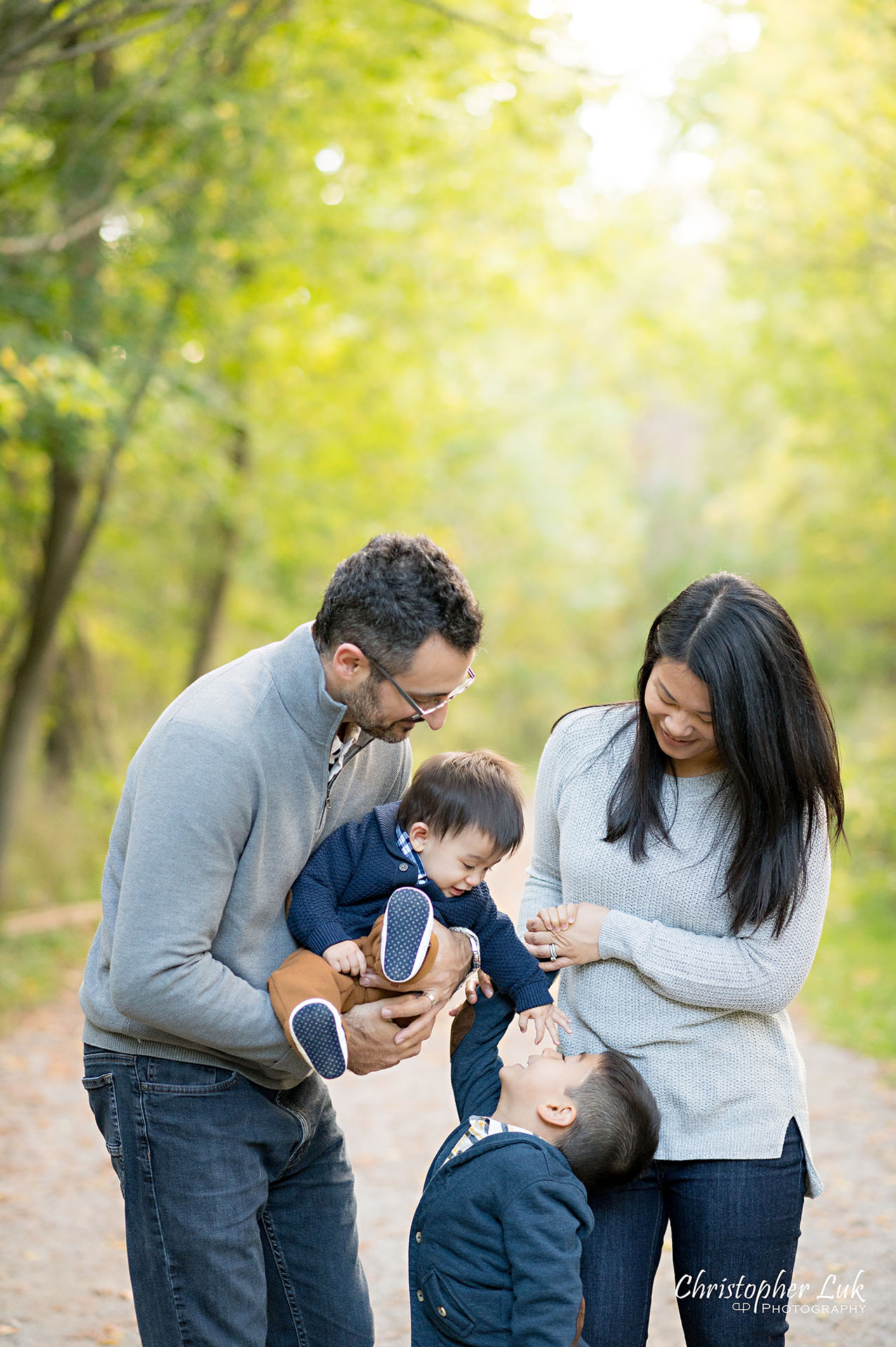 Christopher Luk Family Photographer Toronto Markham Unionville Autumn Fall Leaves Natural Candid Photojournalistic Sons Brothers Baby Boys Father Dad Mother Mom Motherhood Fatherhood Holding Hands Walking Together Trail Pathway Forest Fun Happy Playing with Head Hair