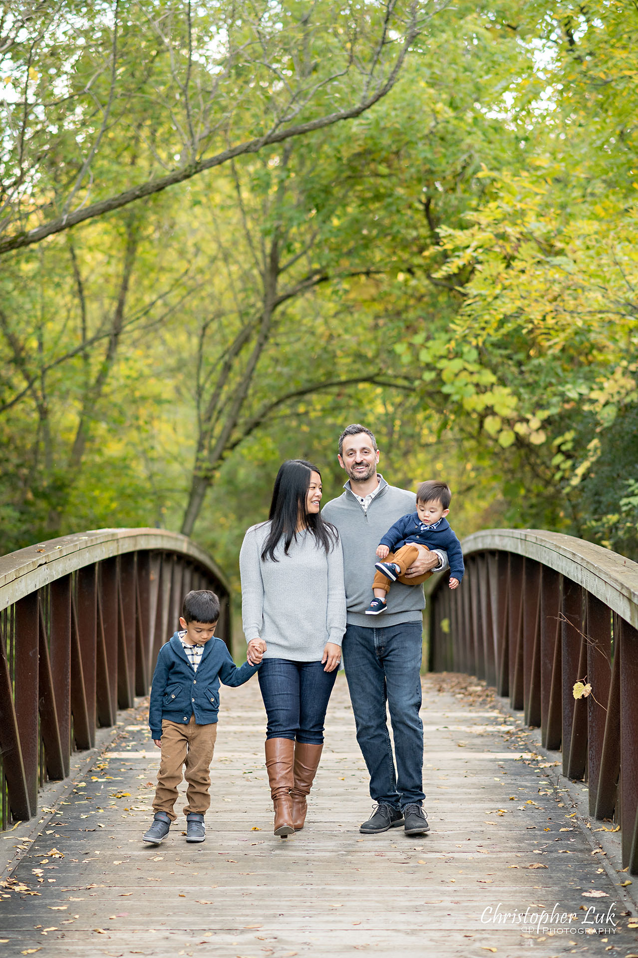 Christopher Luk Family Photographer Toronto Markham Unionville Autumn Fall Leaves Natural Candid Photojournalistic Sons Brothers Baby Boys Bridge Father Dad Mother Mom Motherhood Fatherhood Holding Hands Walking Together