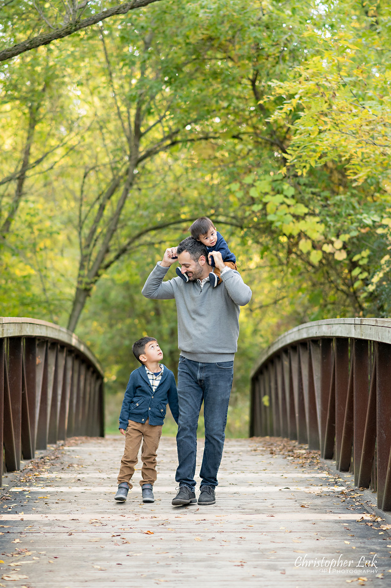 Christopher Luk Family Photographer Toronto Markham Unionville Autumn Fall Leaves Natural Candid Photojournalistic Sons Brothers Baby Boys Bridge Father Dad Fatherhood Holding Hands Walking Carrying Shoulder