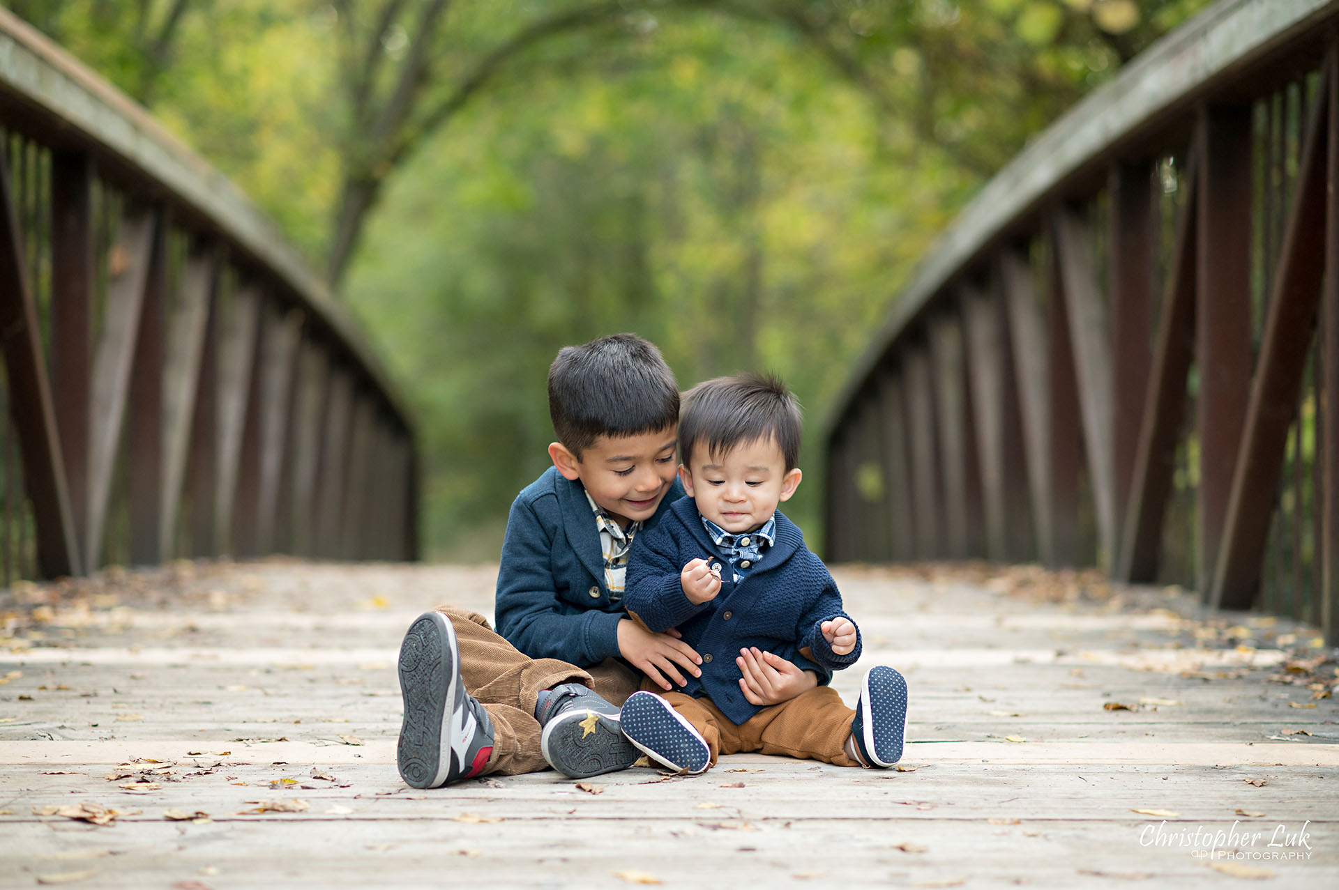 Christopher Luk Family Photographer Toronto Markham Unionville Autumn Fall Leaves Natural Candid Photojournalistic Sons Brothers Boys Hug Sitting Playing Bridge