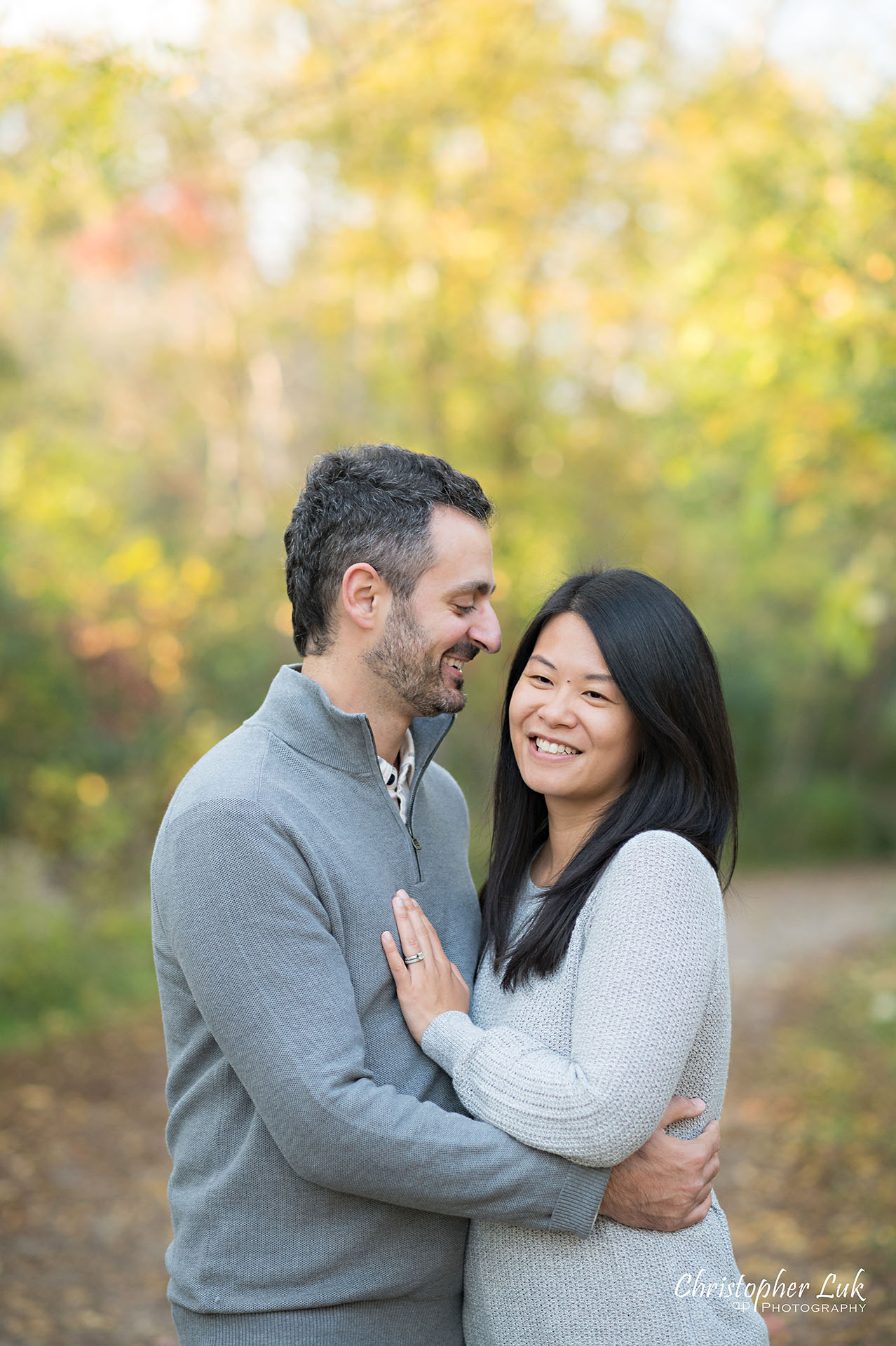Christopher Luk Family Photographer Toronto Markham Unionville Autumn Fall Leaves Natural Candid Photojournalistic Father Dad Mother Mom Motherhood Fatherhood Husband Wife Couple Hug Smile Laugh