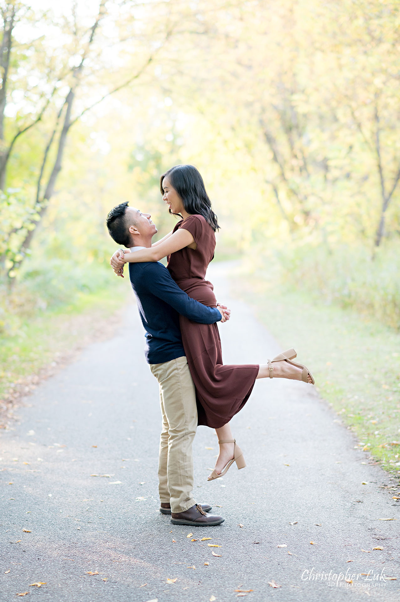 Christopher Luk Toronto Wedding Engagement Session Photographer Autumn Fall Leaves Natural Candid Photojournalistic Bride Groom Holding Hands Walking Together Pathway Hiking Trail Jump Hug Lift Carry