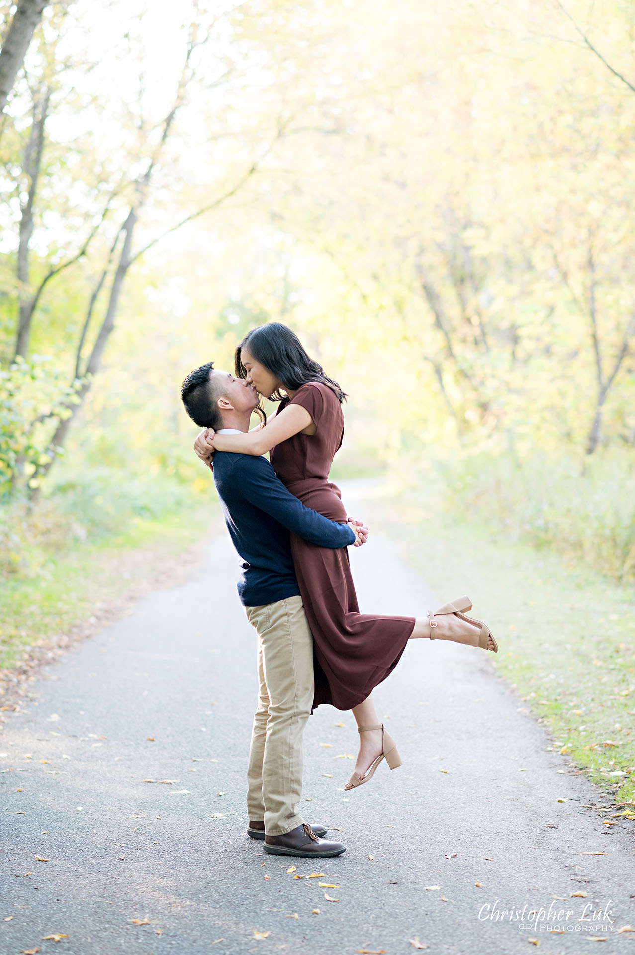 Christopher Luk Toronto Wedding Engagement Session Photographer Autumn Fall Leaves Natural Candid Photojournalistic Bride Groom Holding Hands Walking Together Pathway Hiking Trail Jump Hug Lift Carry Kiss