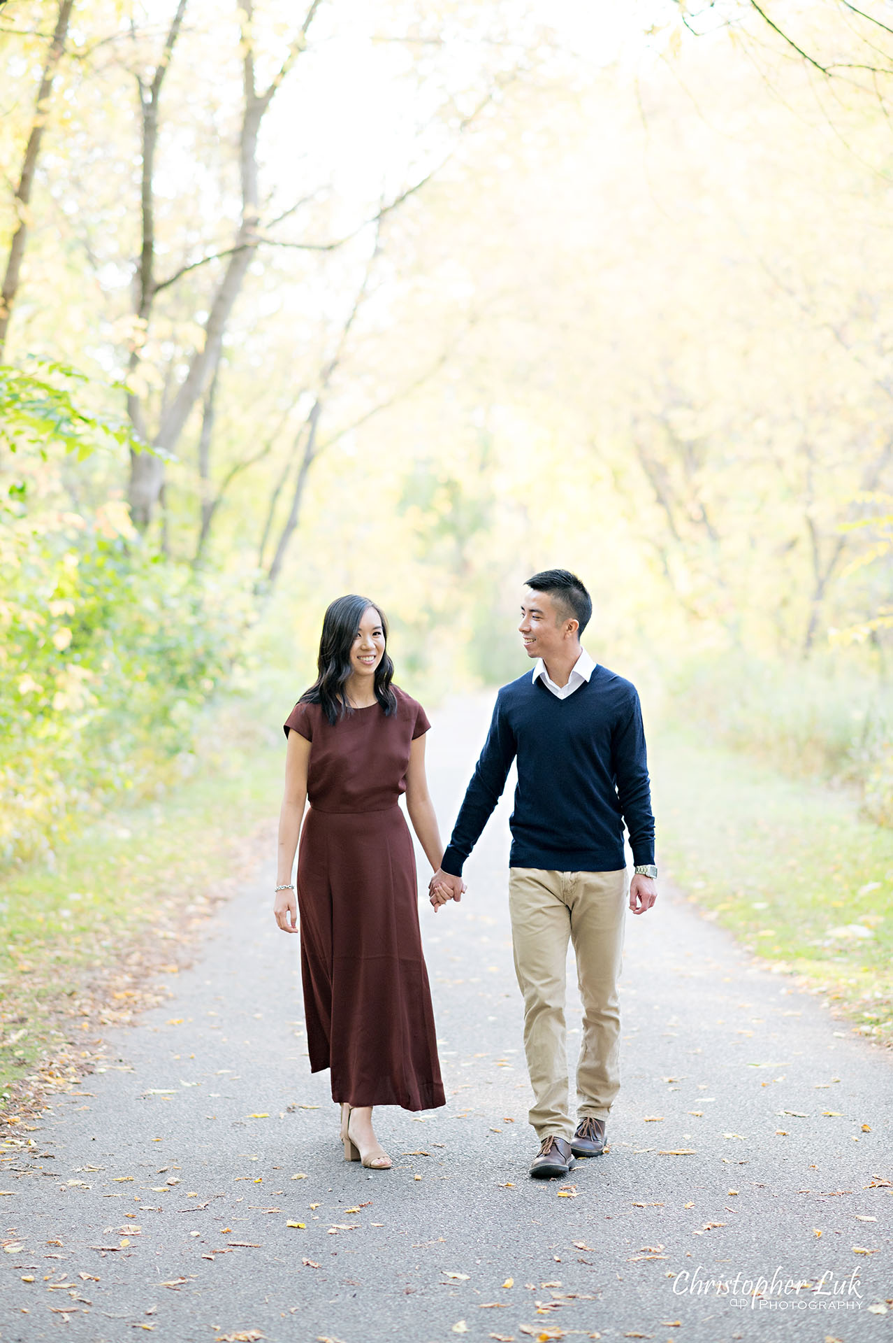 Christopher Luk Toronto Wedding Engagement Session Photographer Autumn Fall Leaves Natural Candid Photojournalistic Bride Groom Holding Hands Walking Together Pathway Hiking Trail