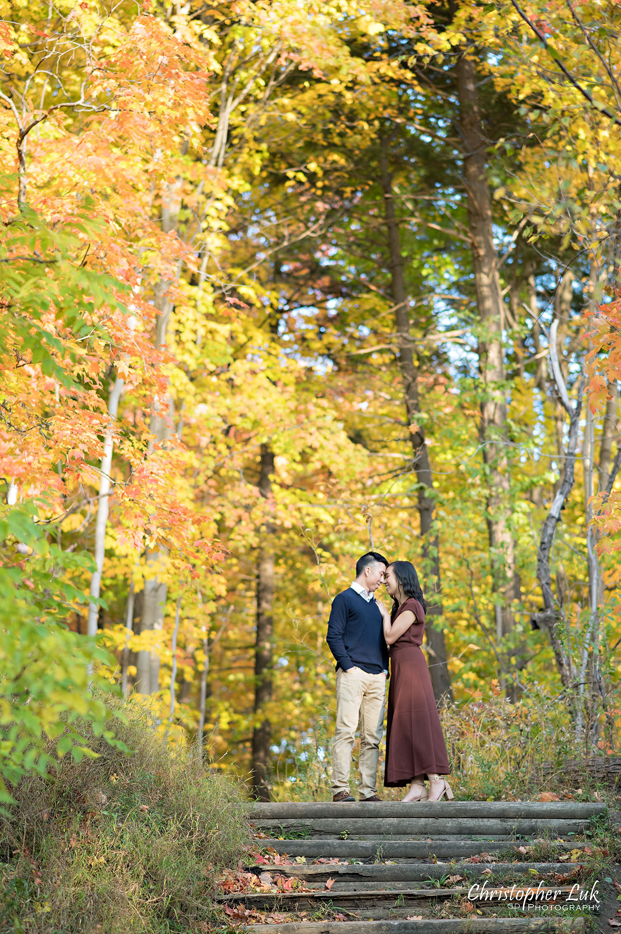 Christopher Luk Toronto Wedding Engagement Session Photographer Autumn Fall Leaves Natural Candid Photojournalistic Bride Groom Hiking Trail Trees Hug Holding Each Other Together Orange Red Yellow Kiss Wood Wooden Stairs Staircase Hiking Trail Steps Vertical