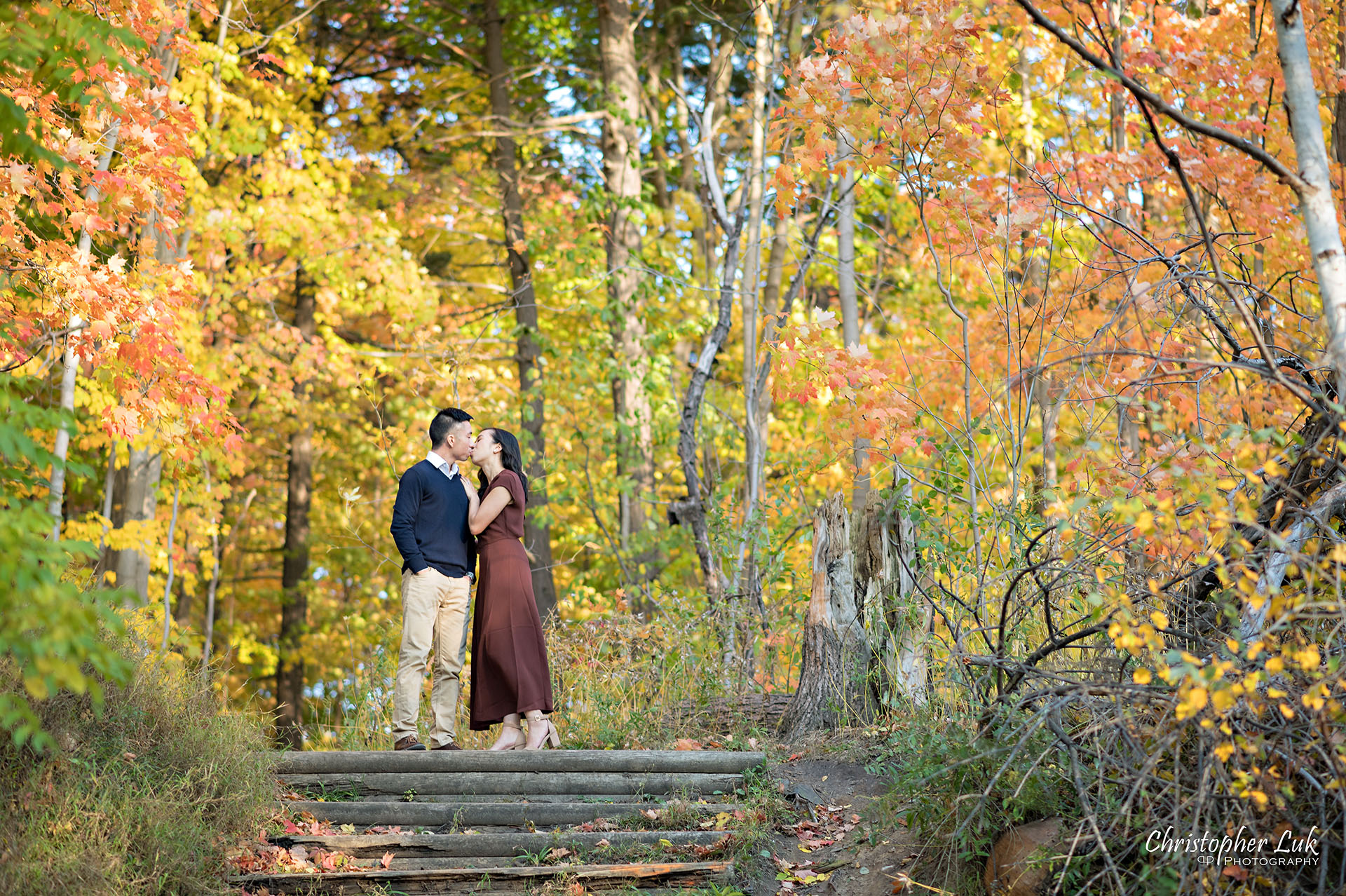 Christopher Luk Toronto Wedding Engagement Session Photographer Autumn Fall Leaves Natural Candid Photojournalistic Bride Groom Hiking Trail Trees Hug Holding Each Other Together Orange Red Yellow Kiss Wood Wooden Stairs Staircase Hiking Trail Steps