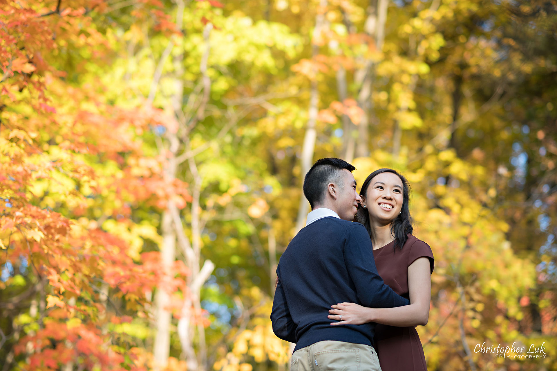 Christopher Luk Toronto Wedding Engagement Session Photographer Autumn Fall Leaves Natural Candid Photojournalistic Bride Groom Hiking Trail Trees Hug Holding Each Other Together Orange Red Yellow