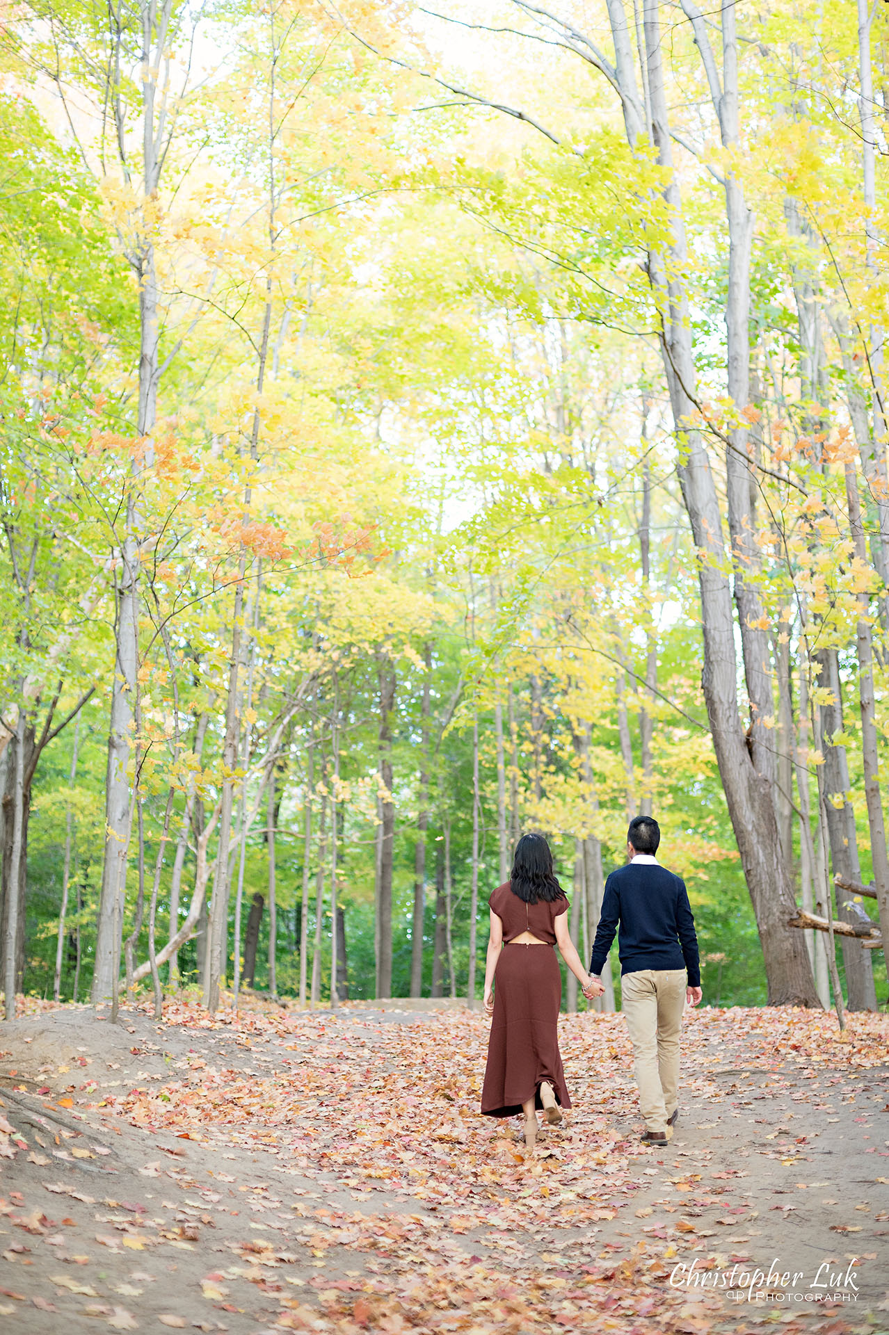 Christopher Luk Toronto Wedding Engagement Session Photographer Autumn Fall Leaves Natural Candid Photojournalistic Bride Groom Hiking Trail Trees Holding Hands Together Walking